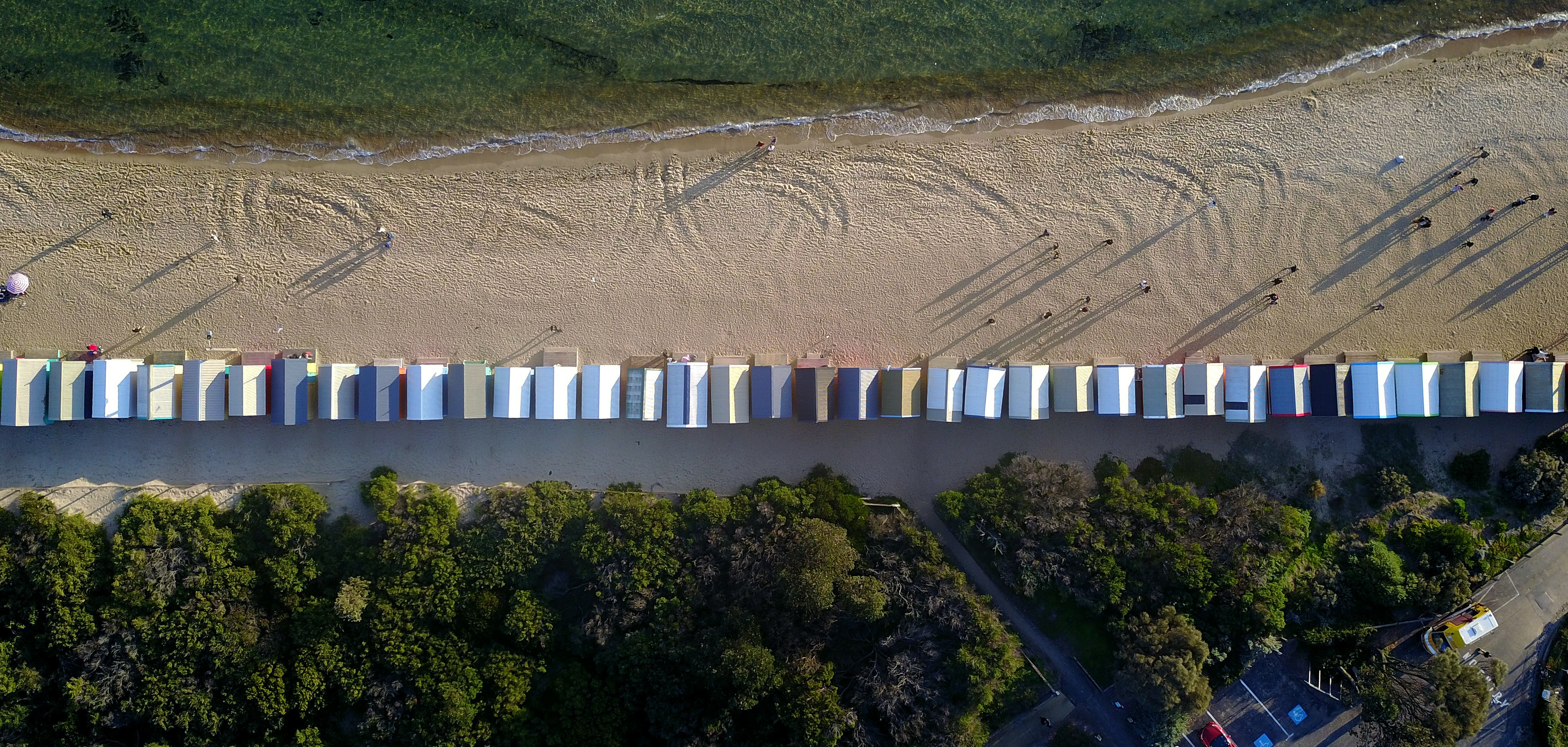 Drone aerial view of beach huts in line at the Brighton sand Beach Boxes