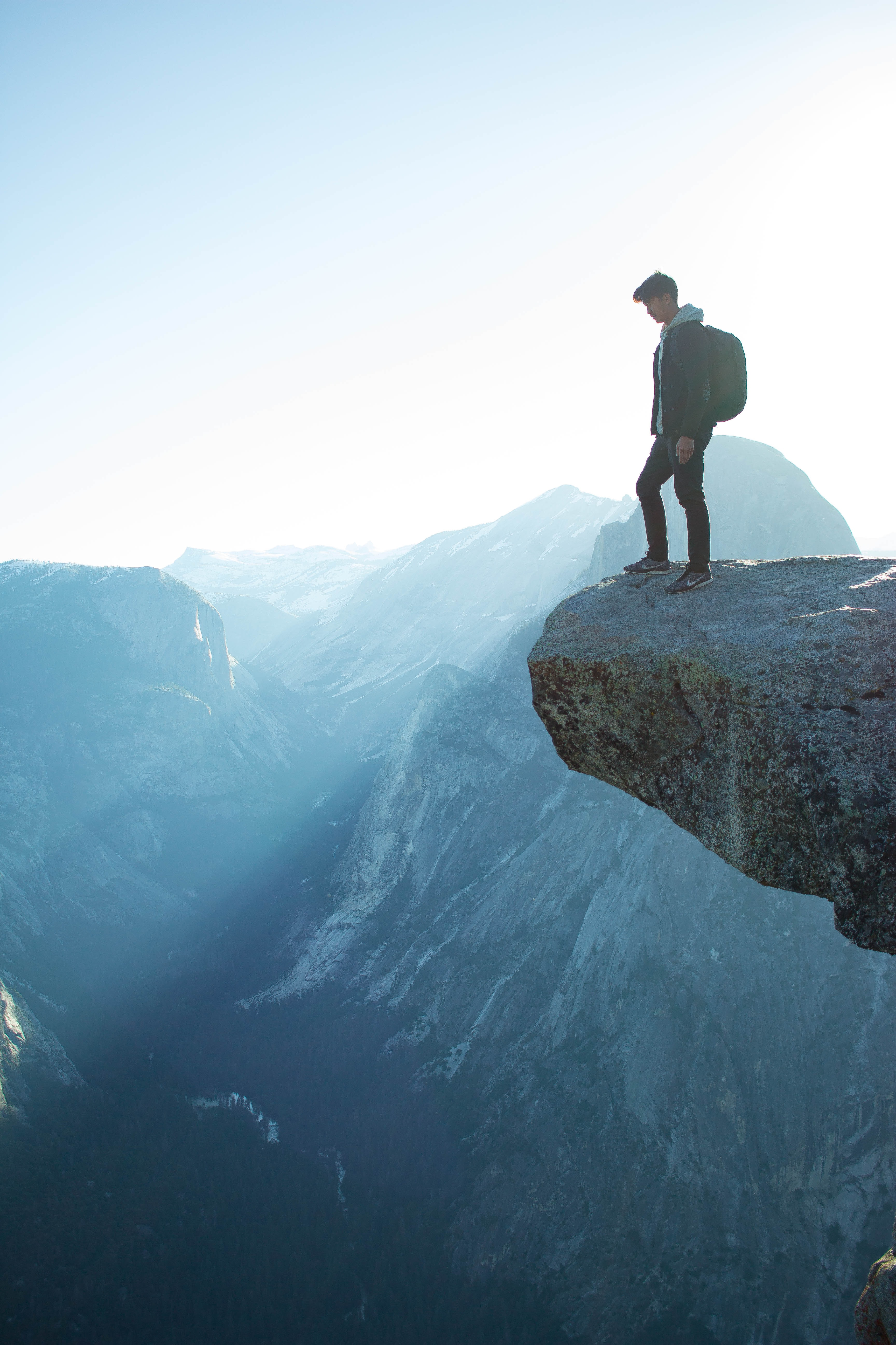 A man with a backpack approaching the edge of a ledge over a precipice