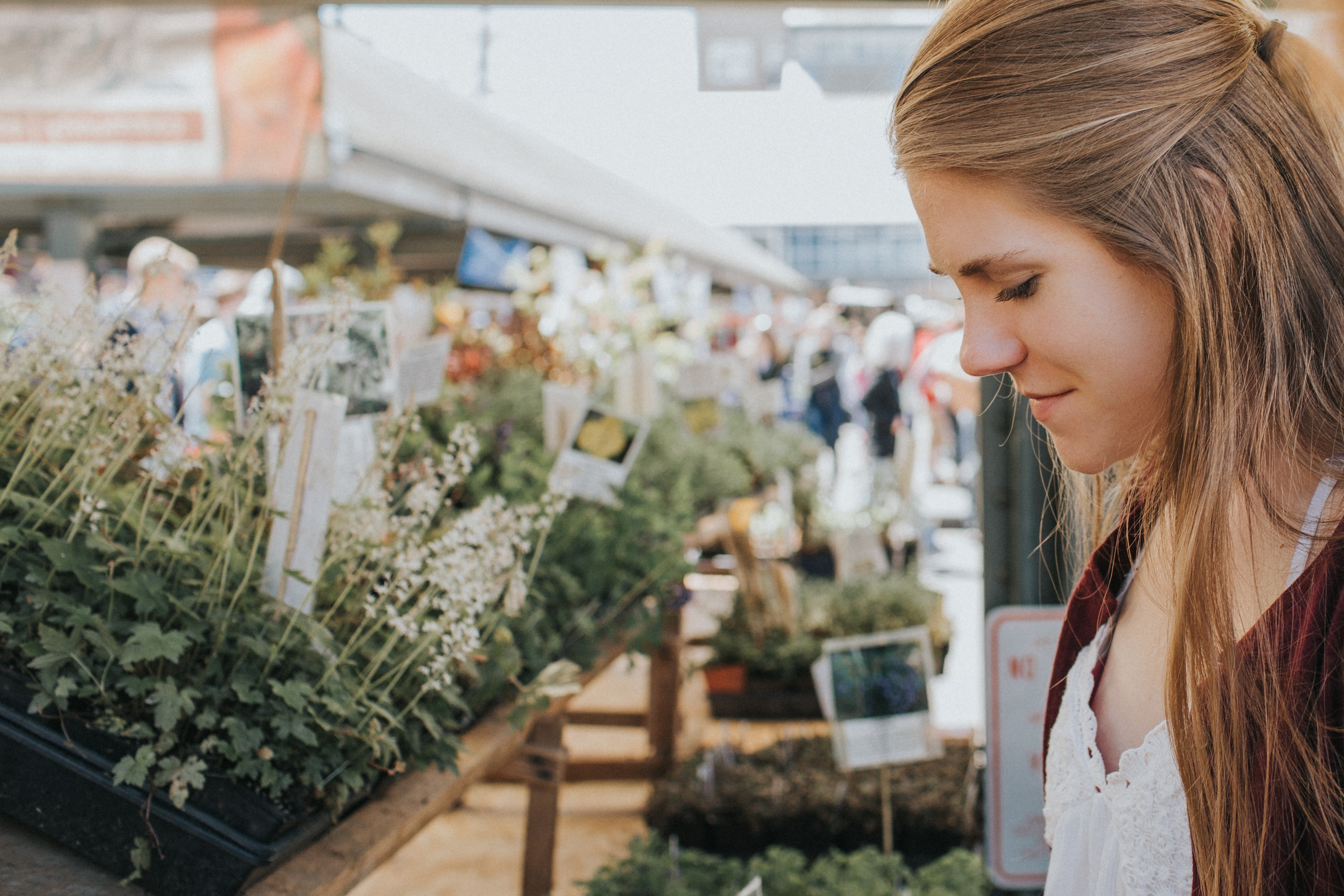 A smiling woman near a stall with green plants at a farmers' market