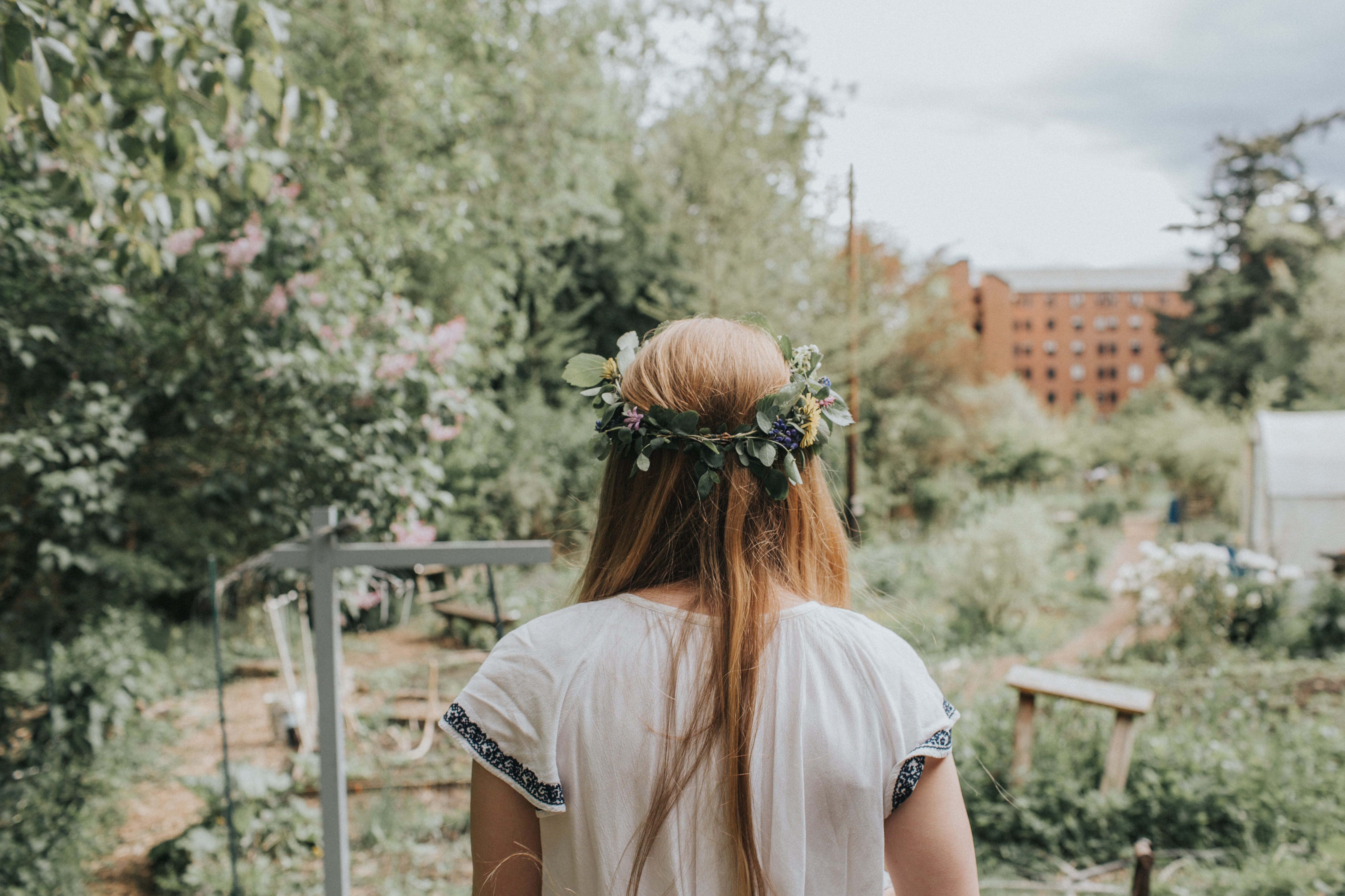 Back view of a woman wearing a floral crown in a garden in The Outback Farm.