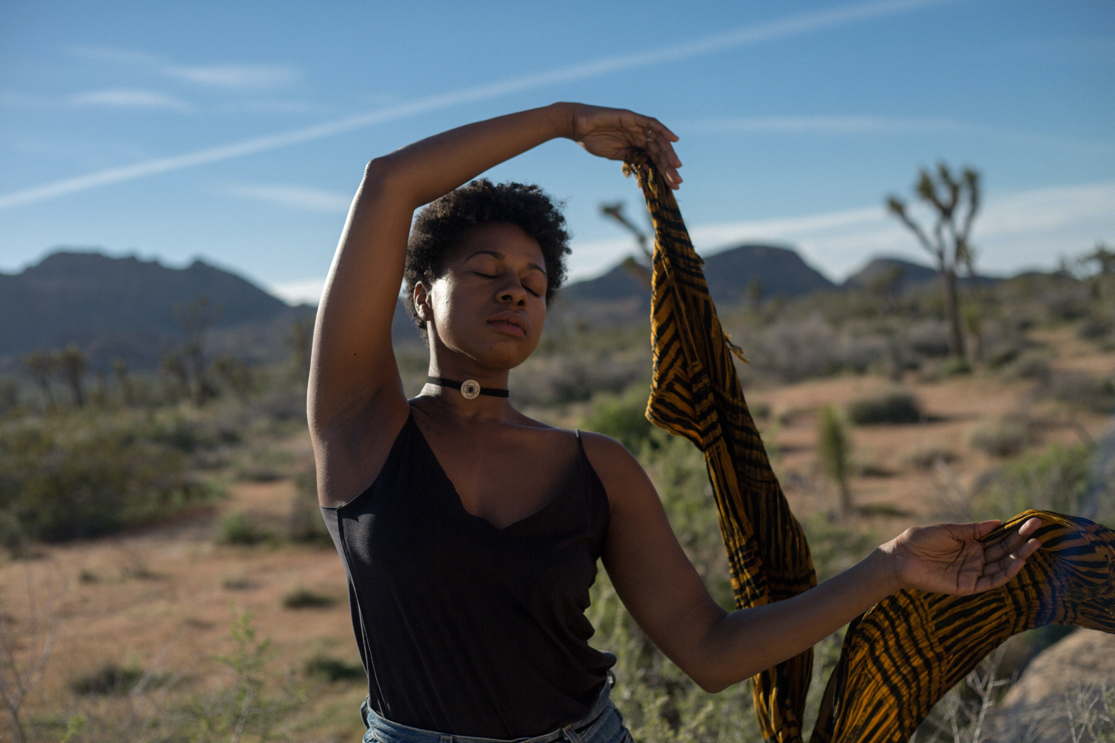 Woman dances peacefully with eyes closed in Joshua Tree desert