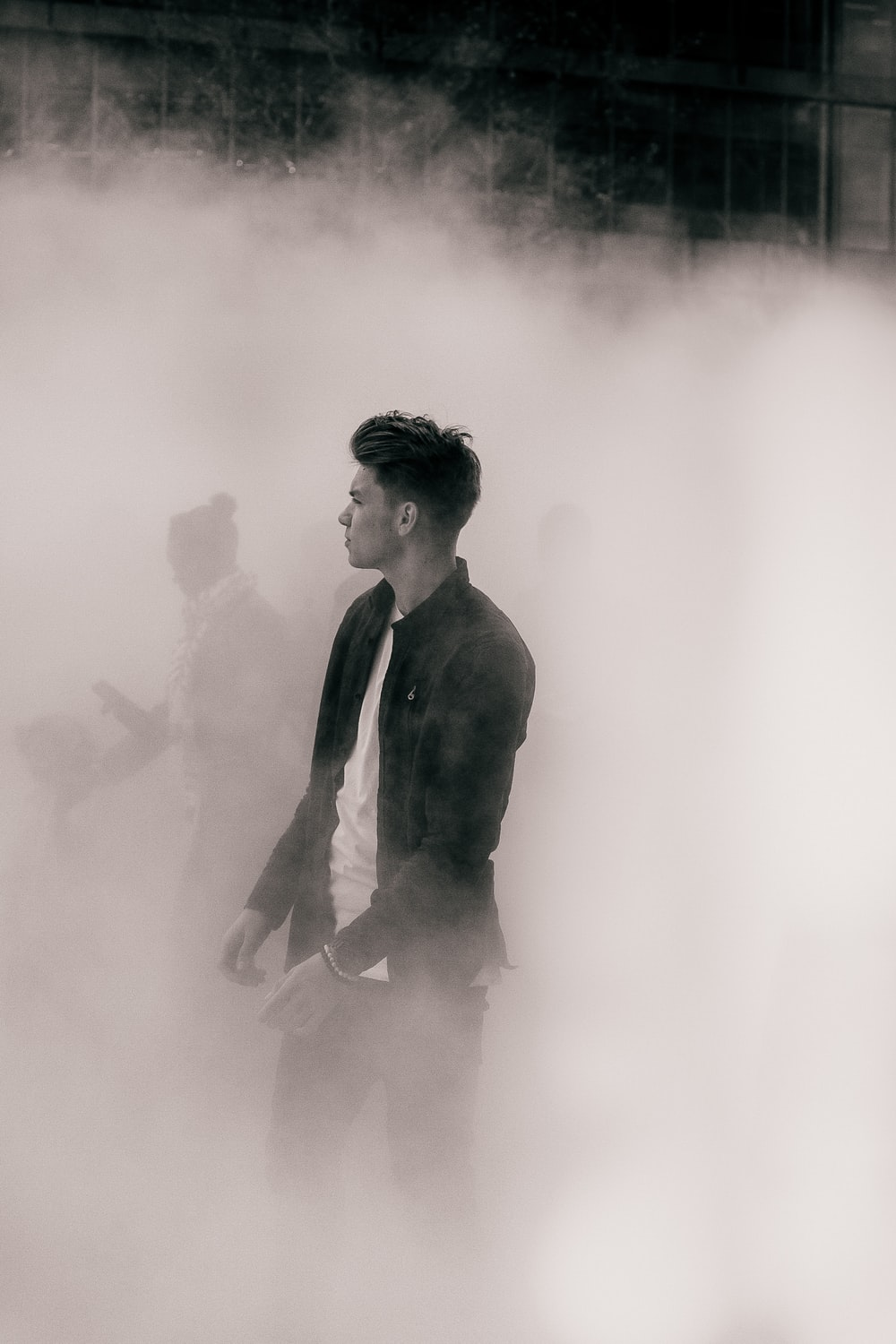 Fashionable man walks out of the fog away from the crowd