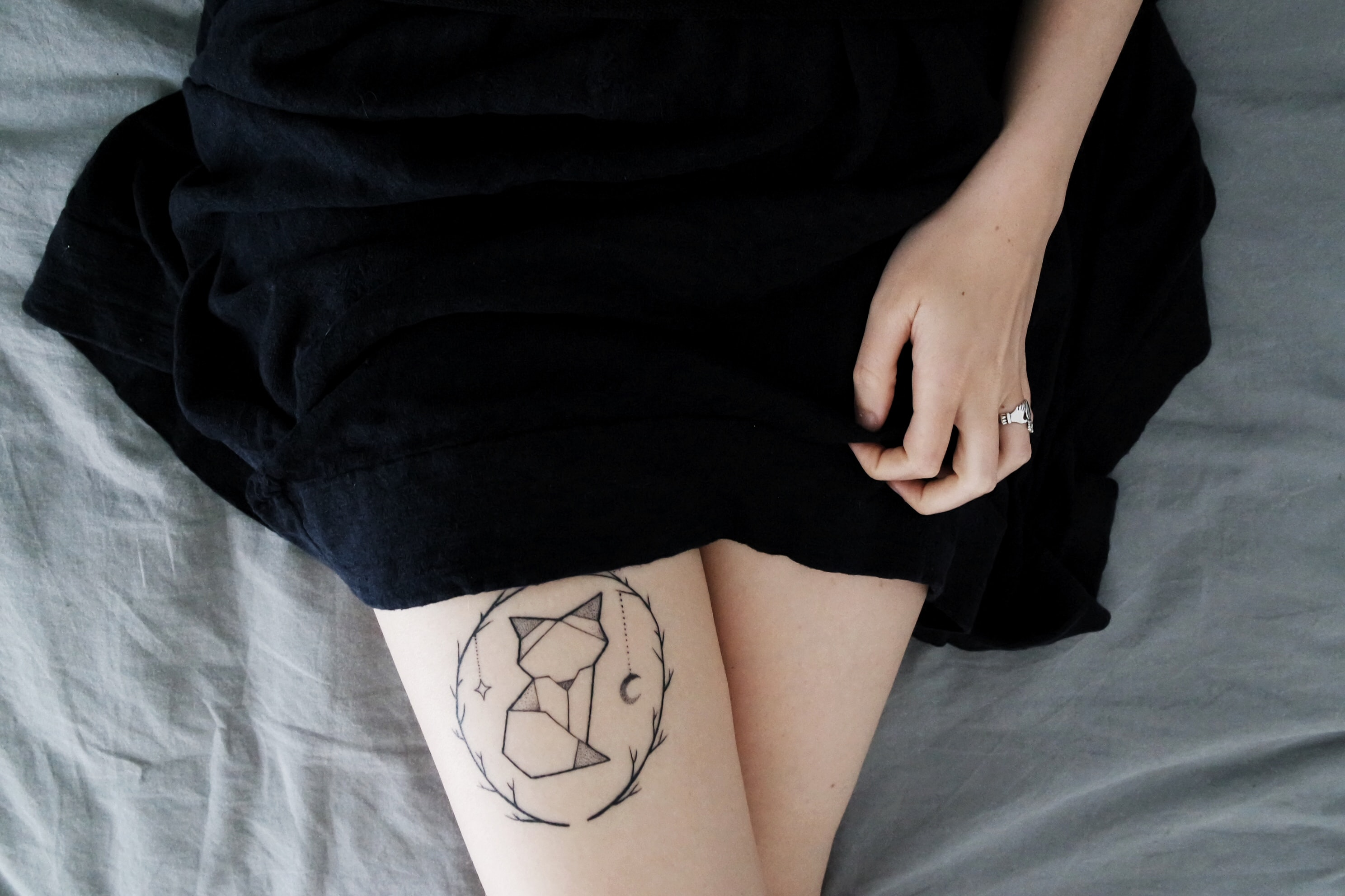 woman lying on bed sowing cat dreamcatcher tattoo on right leg during daytime