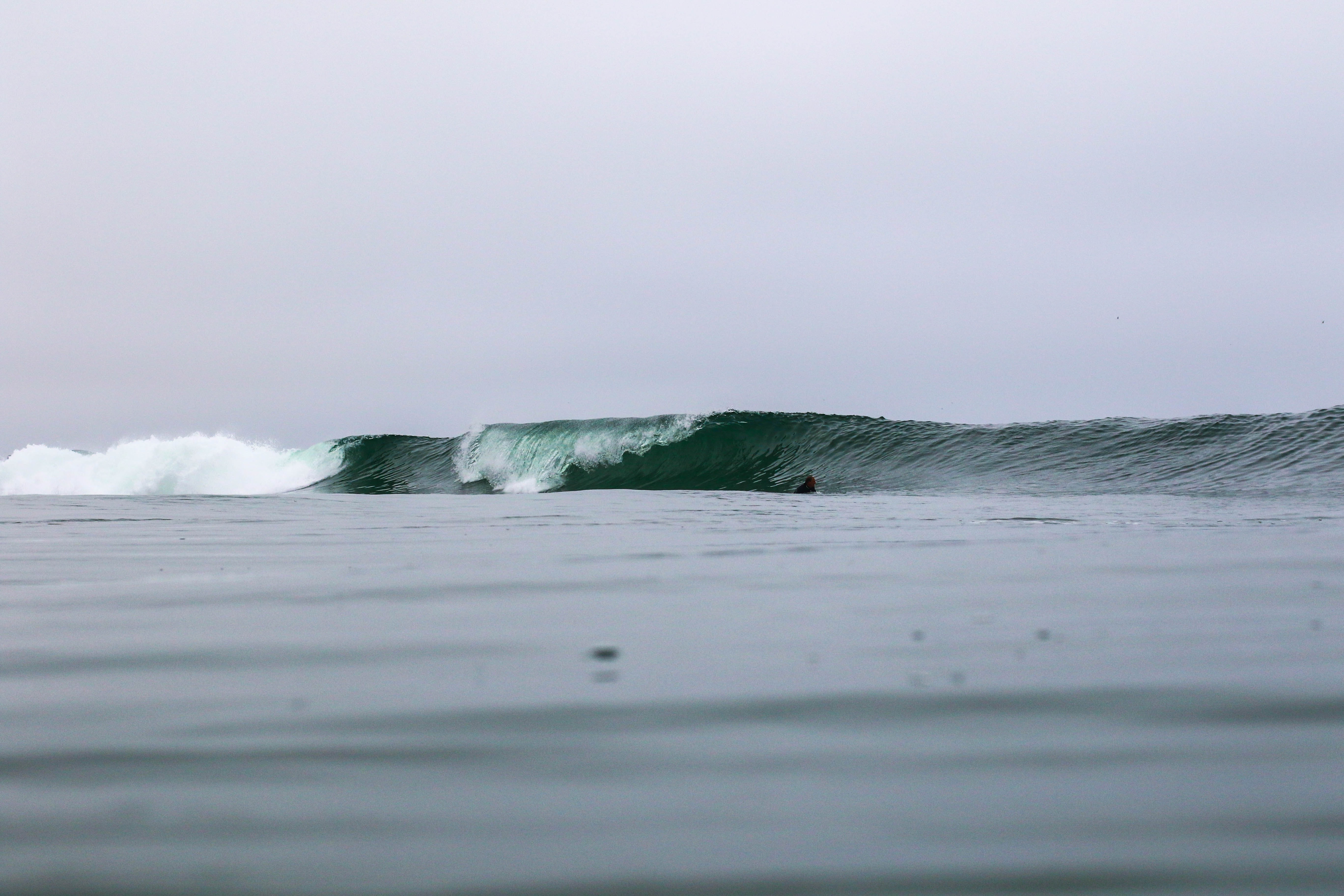 Surfer in the water going towards big surf wave at Newport Beach