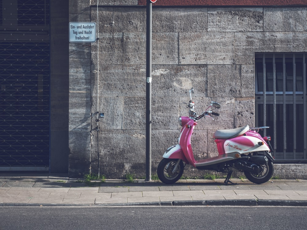 parked pink motor scooter
