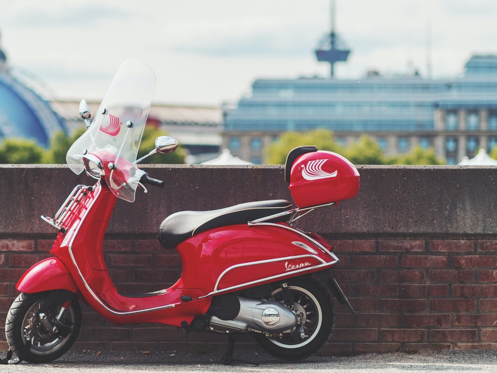 red motor scooter parking near wall