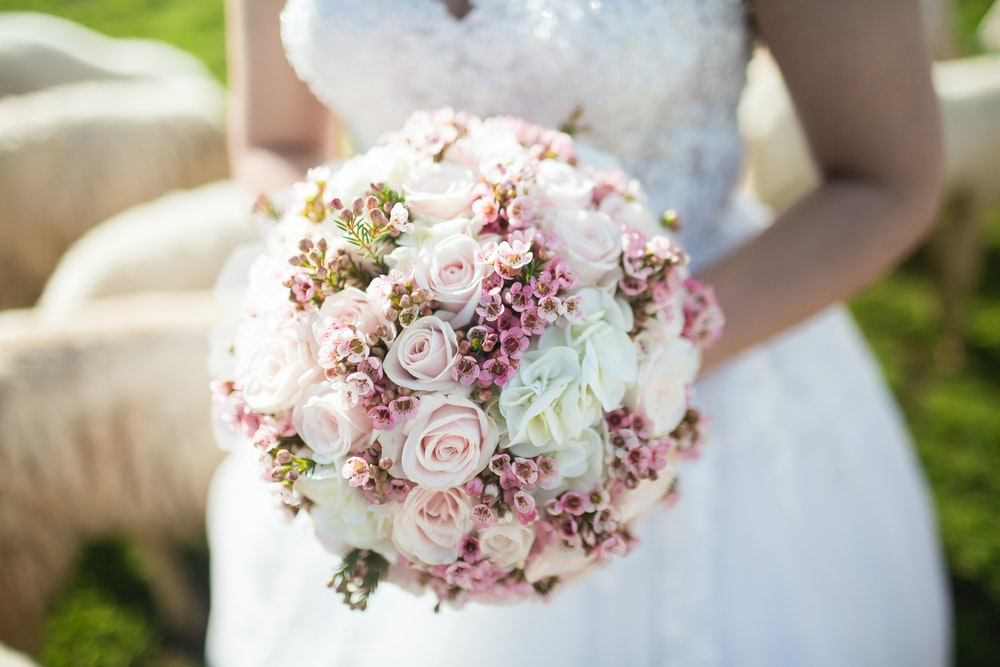 A bride with a round bouquet of white and pink flowers
