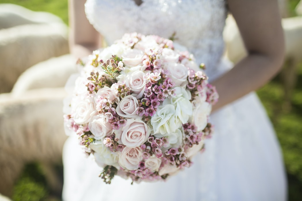 a bride holding a round wedding bouquet