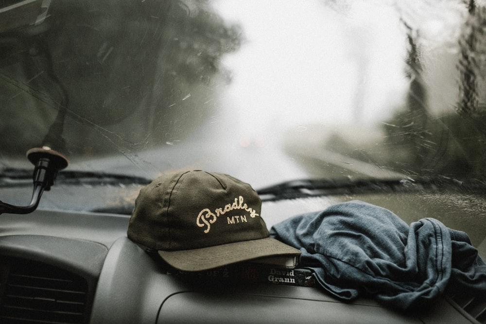 black and white baseball cap near grey shirt on top of glove compartment inside car
