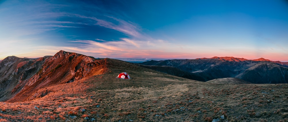 red and white camping tent on top of the mountain during daytime