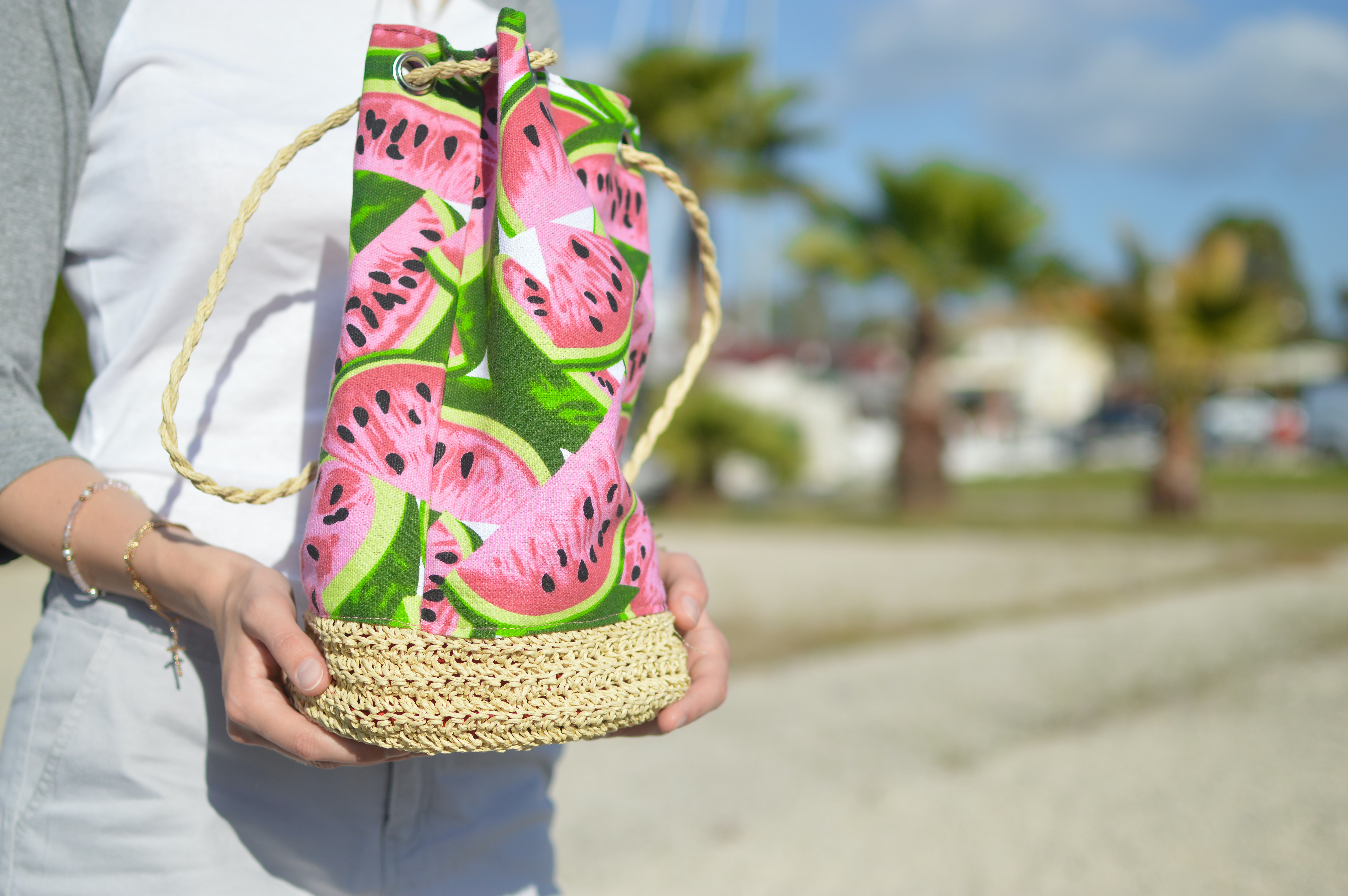 A person holds a purse printed with wedges of watermelon on the beach in Corfu