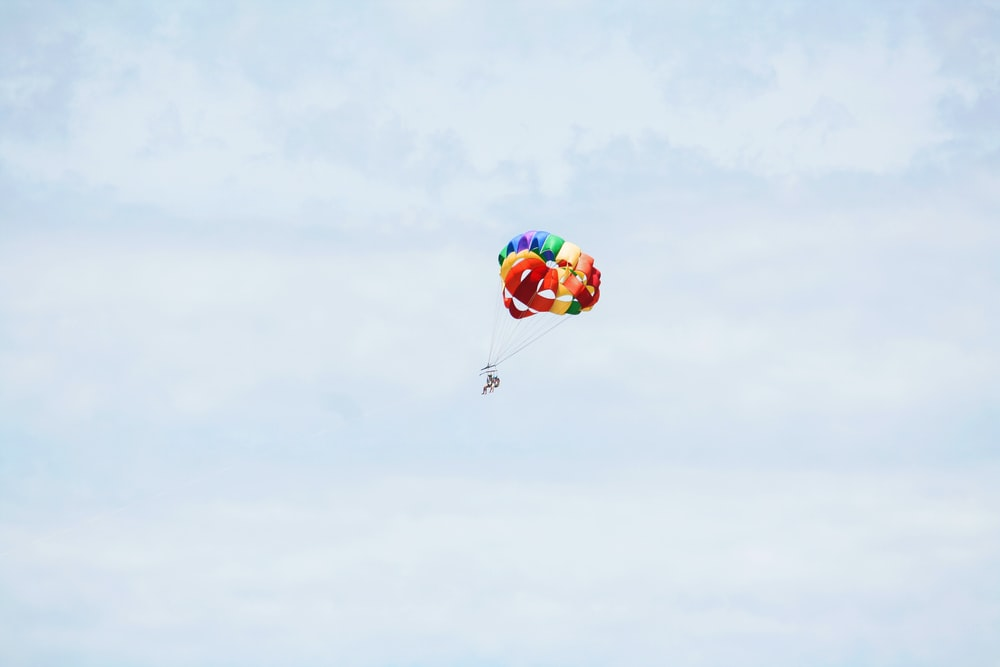 person on parachute sky diving under cumulus clouds