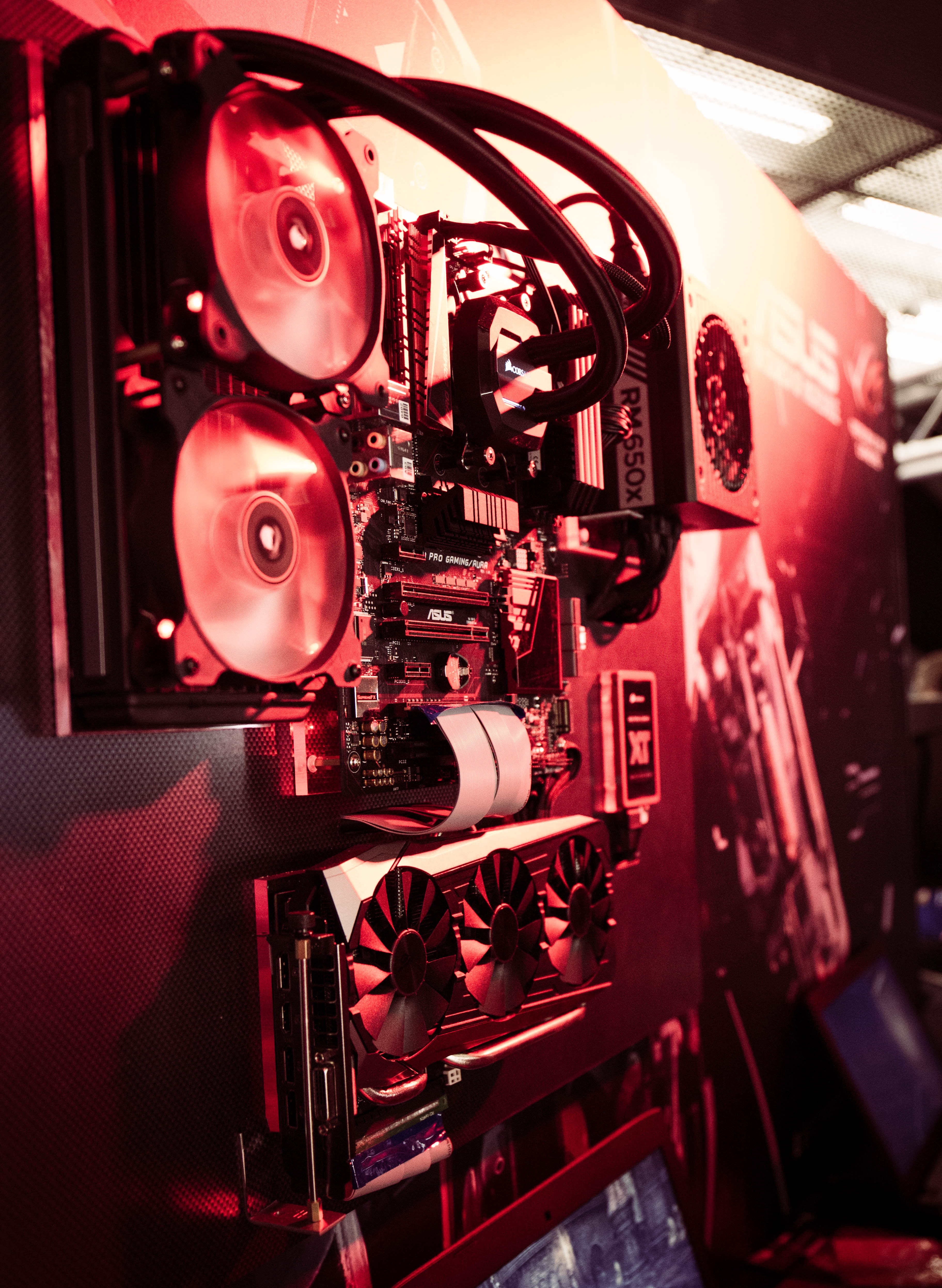 A computer without the case showing the motherboard, cooling fans, graphics cards, and power supply mounted on a red-lit wall labeled ASUS in a gaming convention