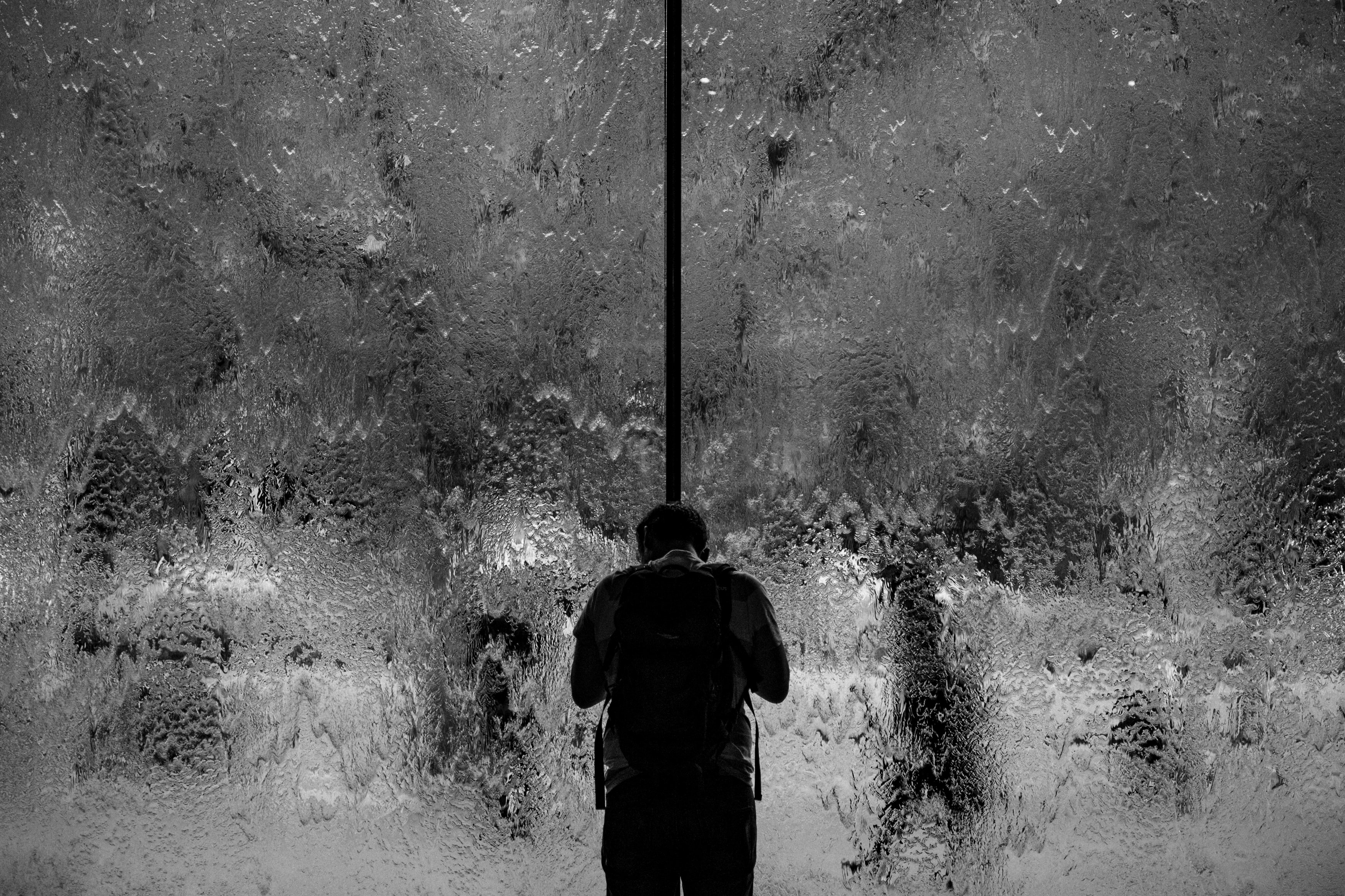 Black and white shot of man from behind standing near of window covered in water, Melbourne