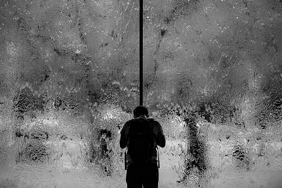man standing on glass wall with pouring water sorrow teams background