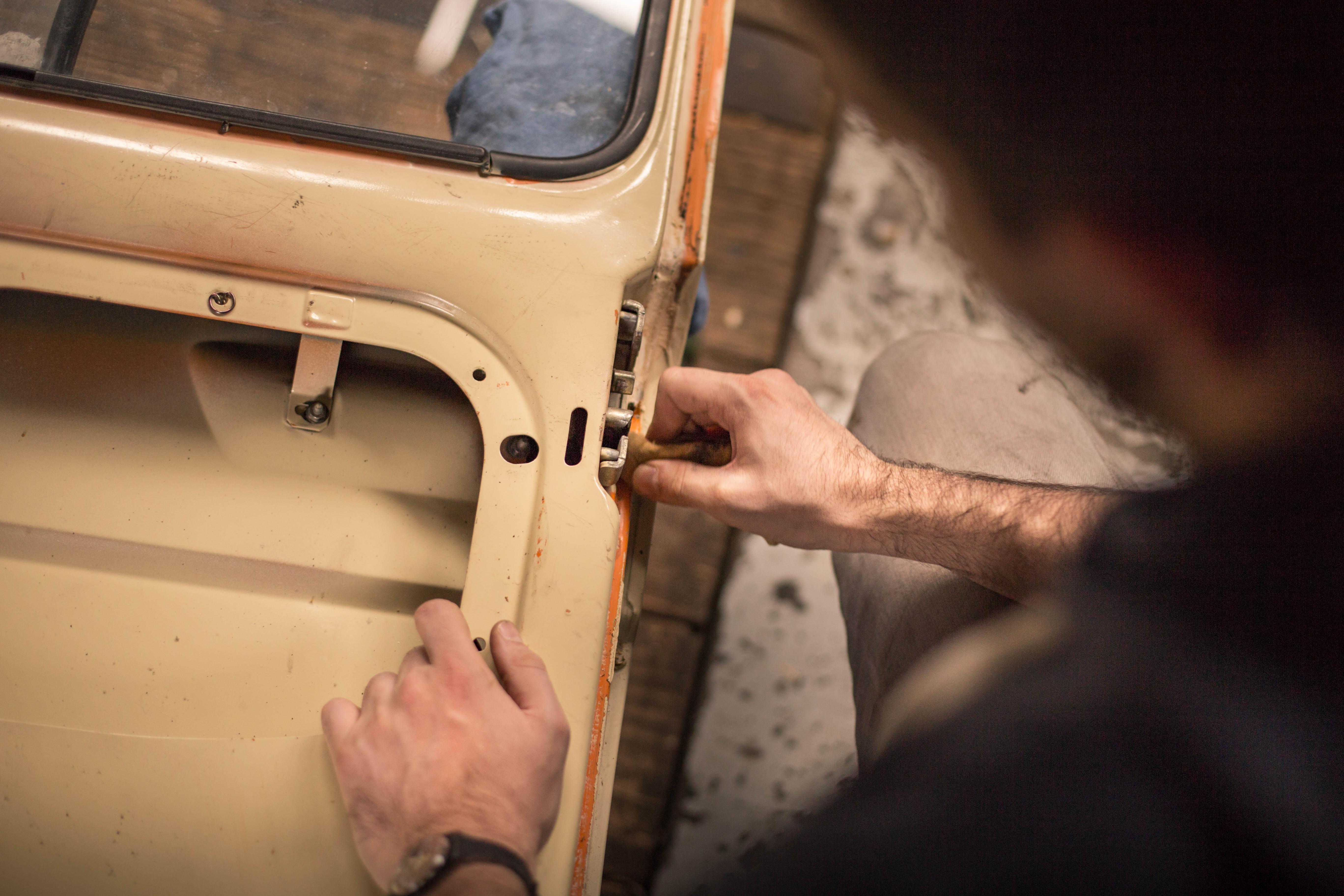 A man adjusting the lock mechanism on a car door