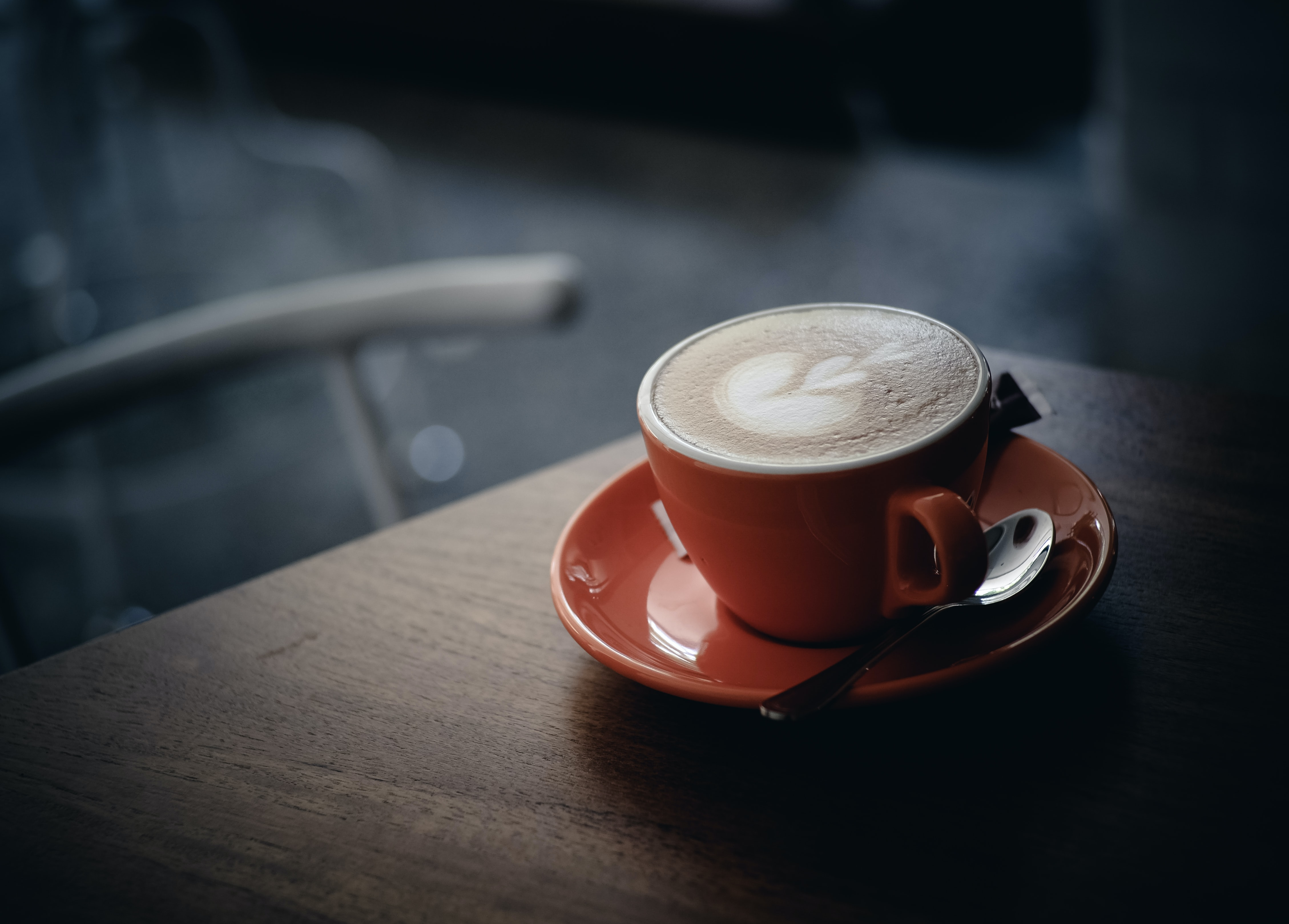 A cup of coffee in an orange mug on an orange saucer with latte art in Bandung