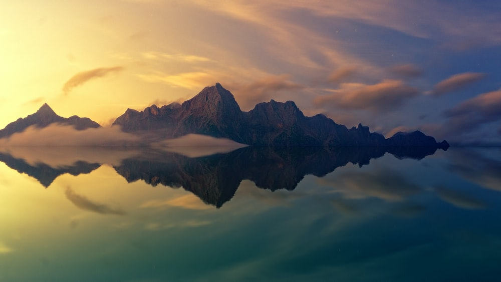 brown mountain mirrored in body of water
