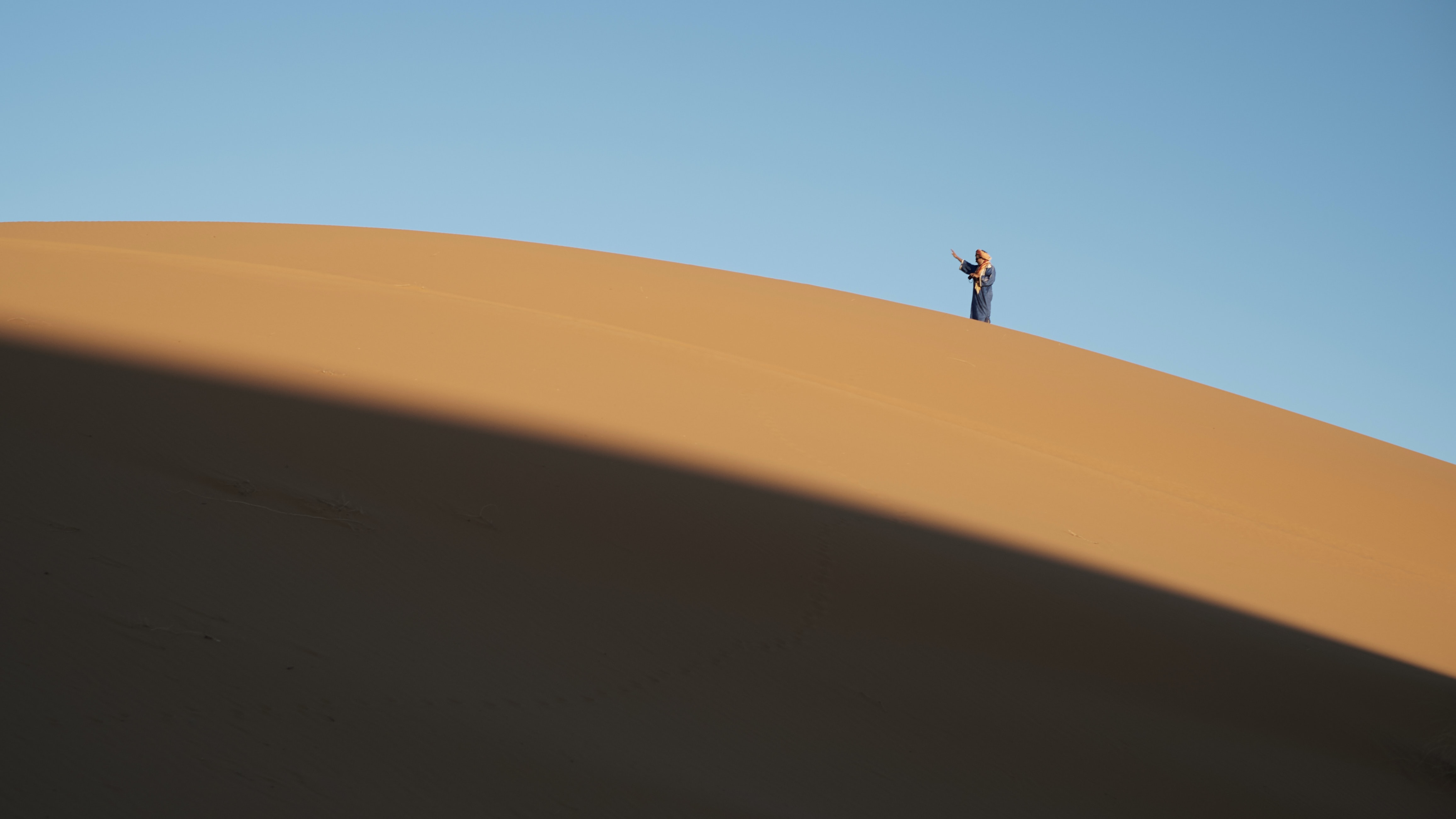 Person stands on the top of a sand ridge in the Sahara Desert