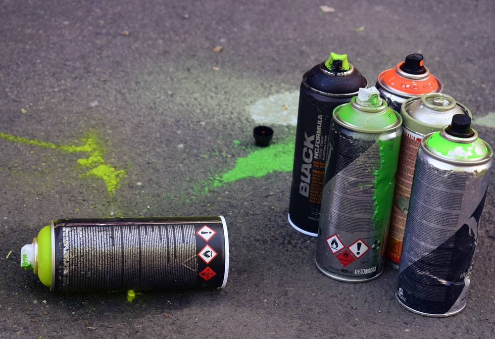Used spray cans sitting on the ground.