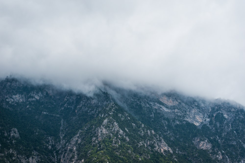 grass covered mountains under white cloudy sky