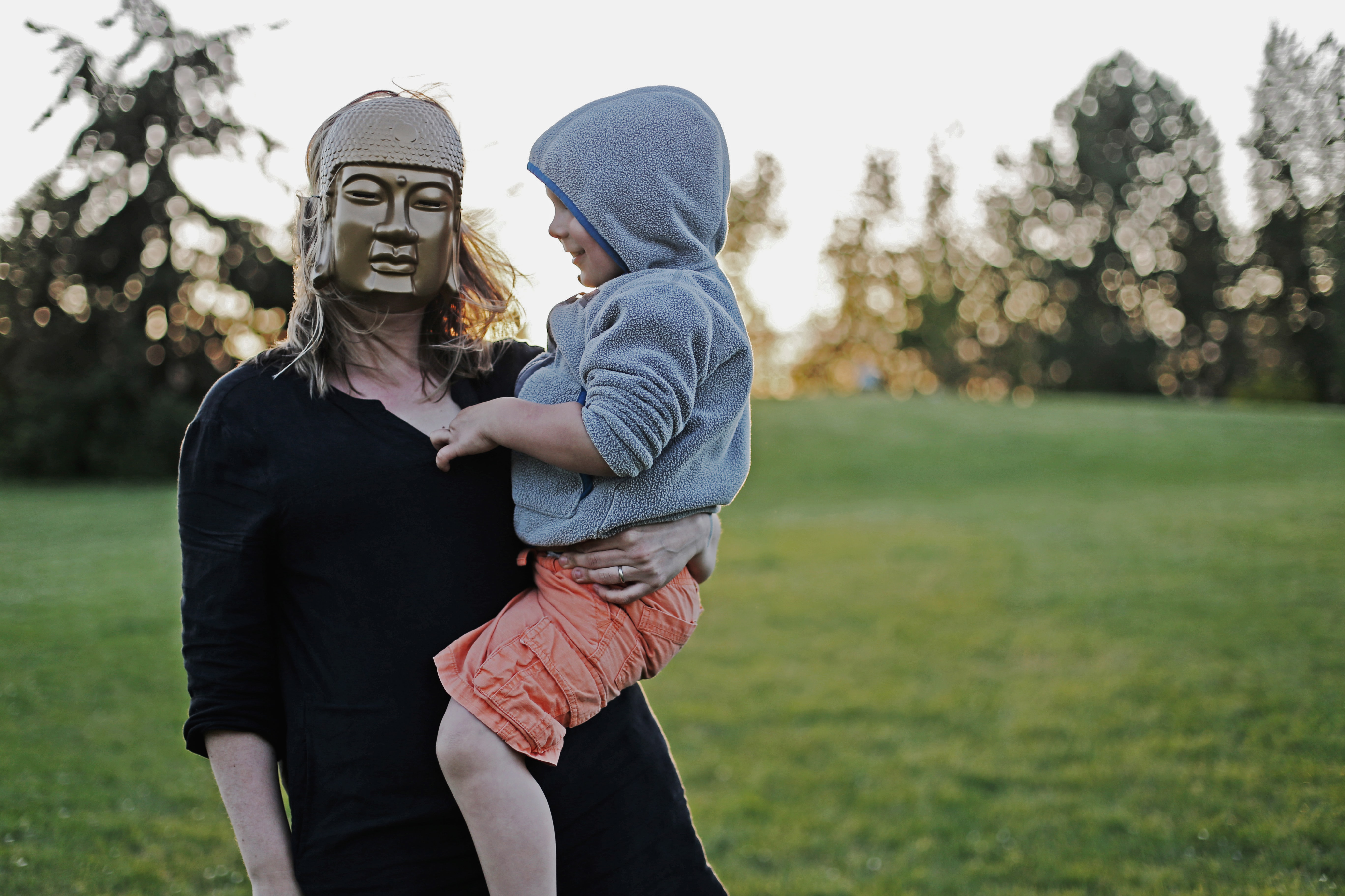 A woman wearing a Buddha mask is carrying a child wearing a hooded jacket.