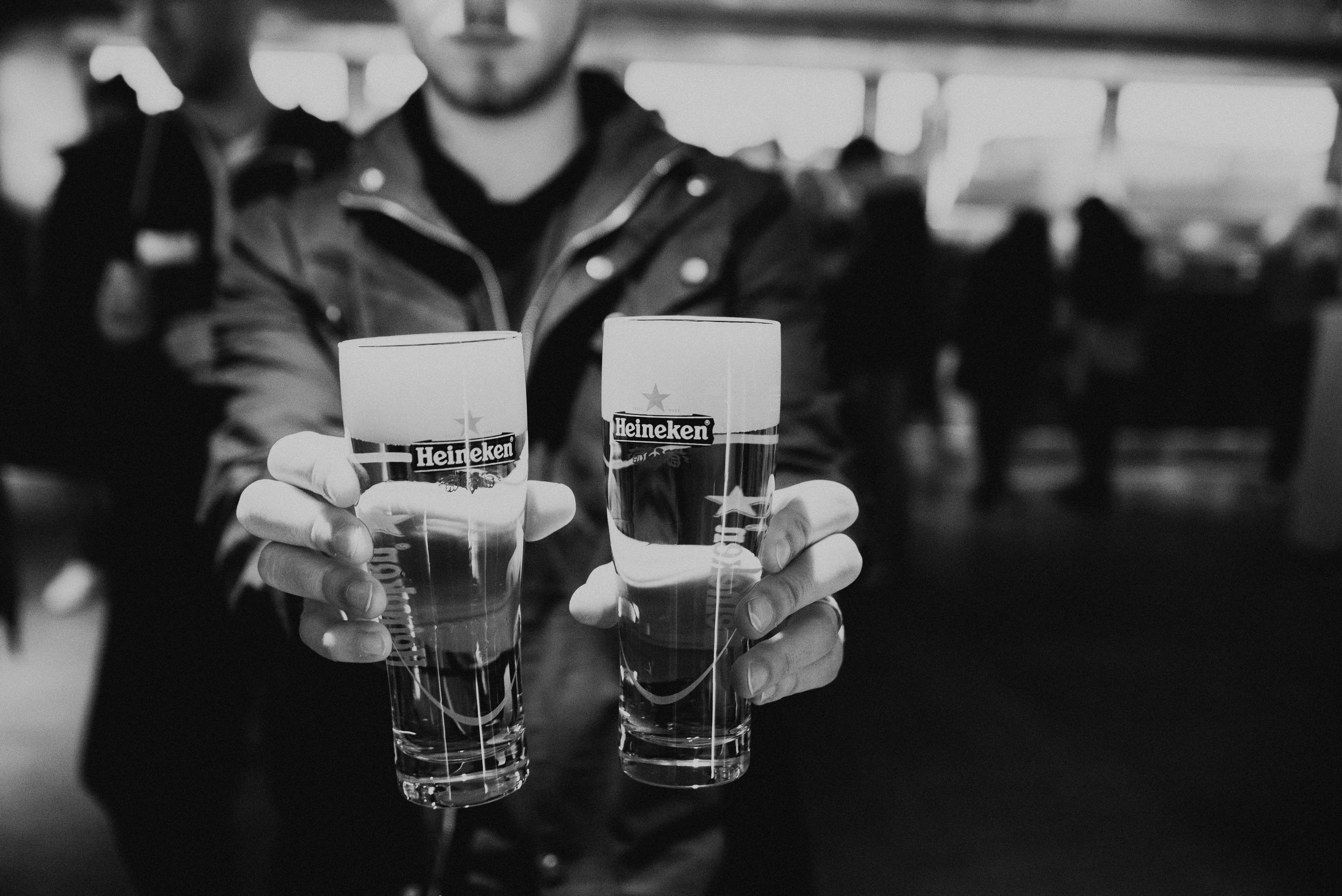 Macro view of a man holding Heineken glass cups with Heineken experience in black and white