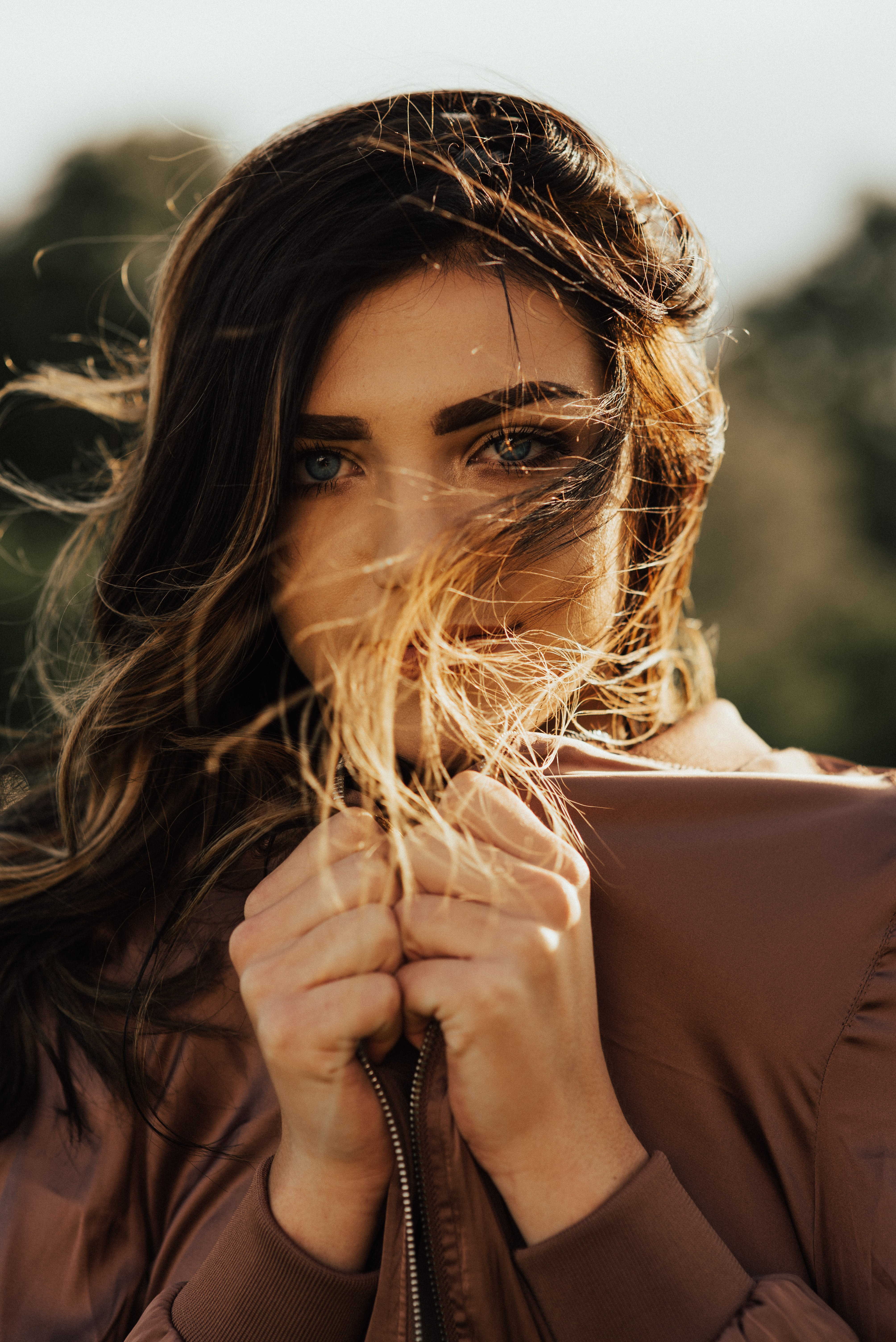A woman in a brown jacket with her hair blowing in the wind in Salt Lake City