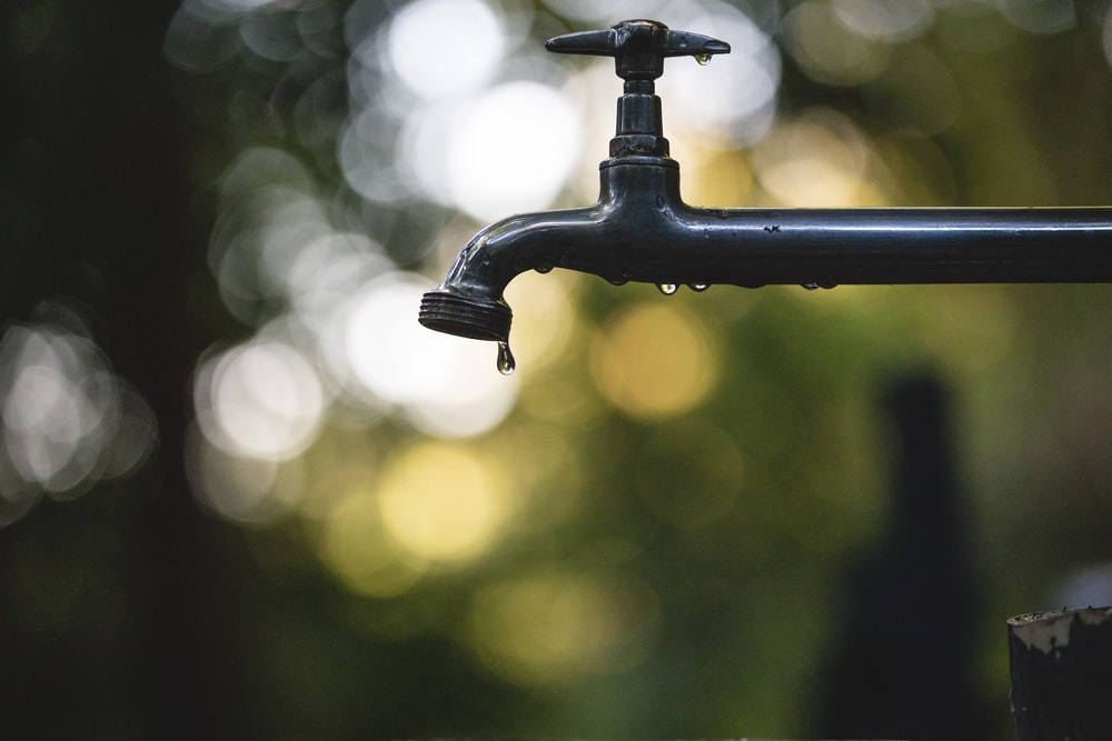 tilt shift lens photography of black steel faucet