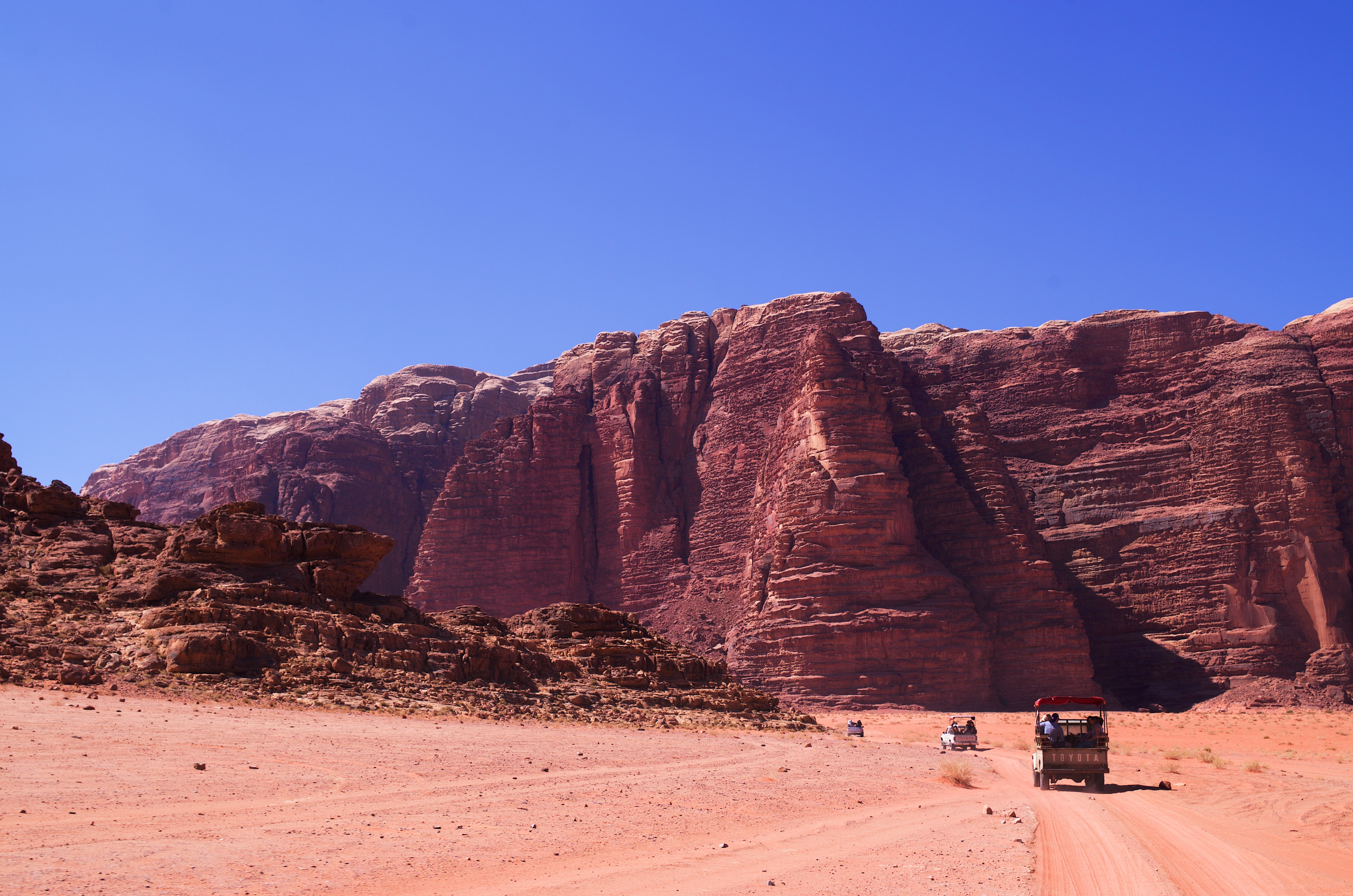 Tourists ride toward rocky cliffs in the desert of Wadi Rum Protected Area