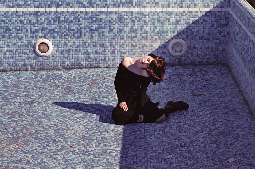 woman sitting inside the empty pool