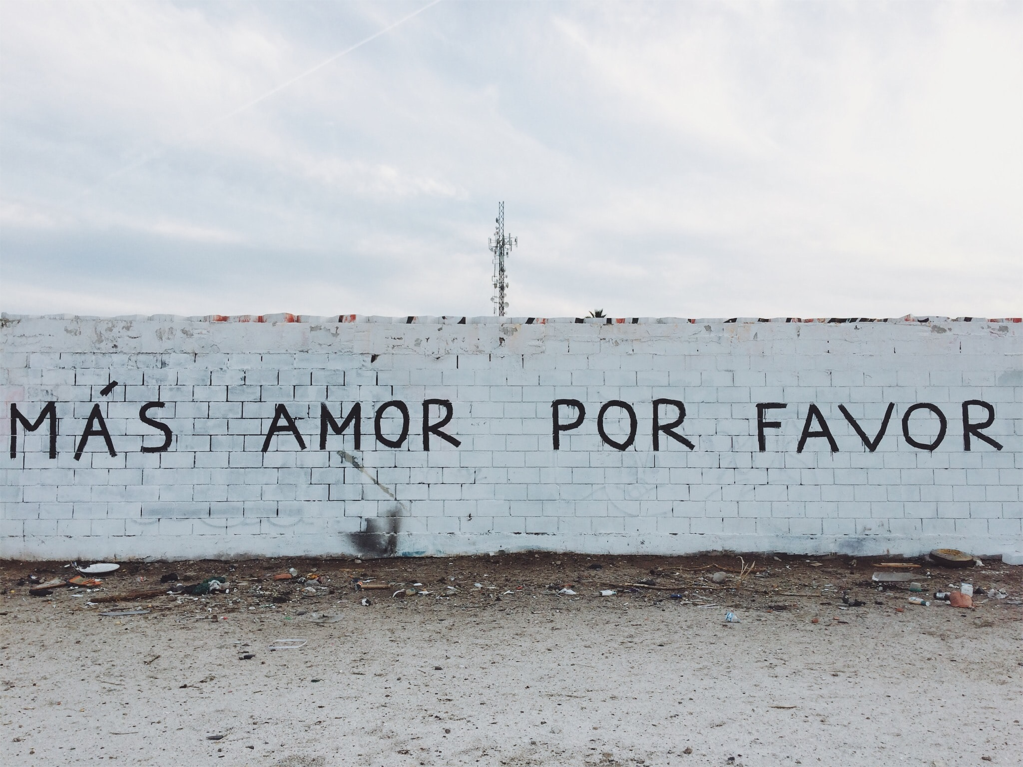 A white brick wall with a painted message in Spanish in Mexicali