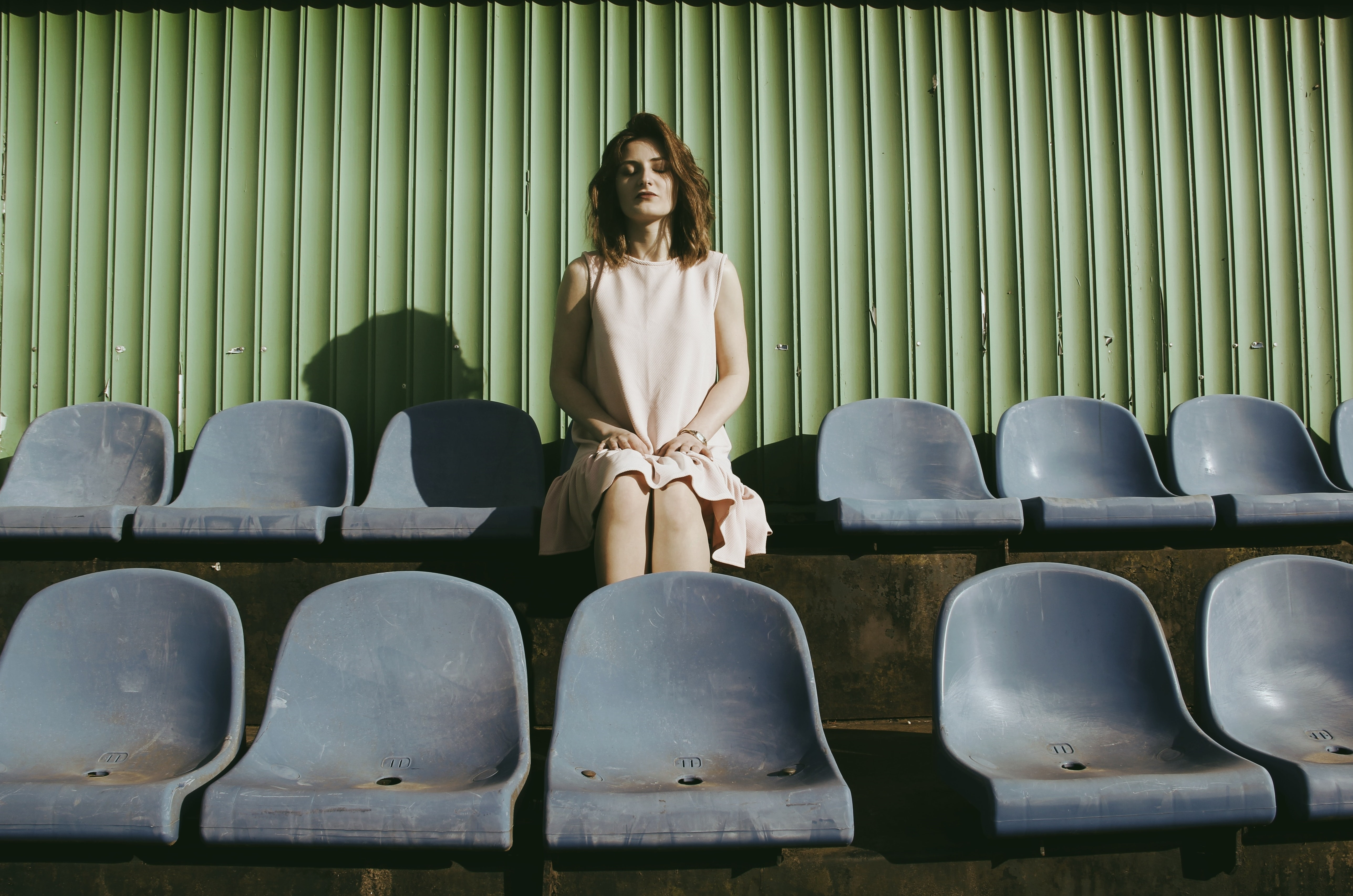 A woman in a dress sits in a row of chairs before a green wall