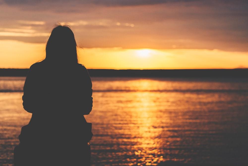 silhouette of woman sitting near bay