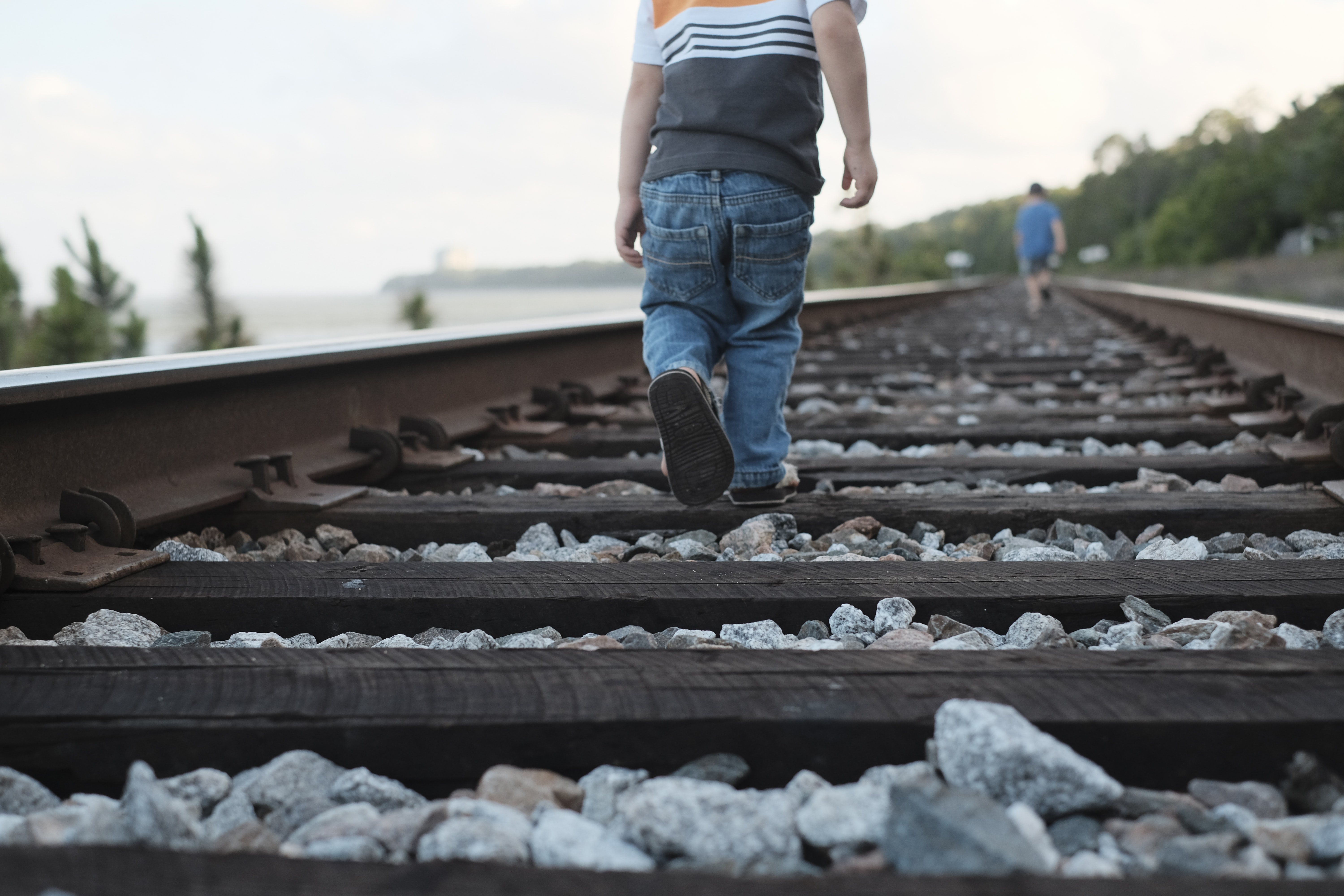 toddler walking on train rail during daytime