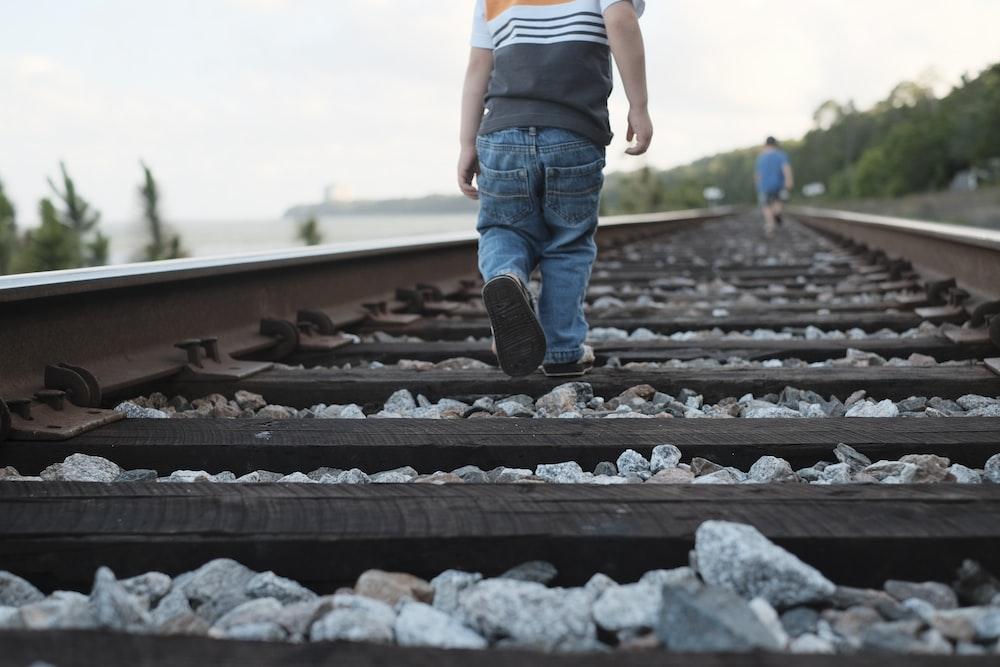 toddler walking on train rail during daytime