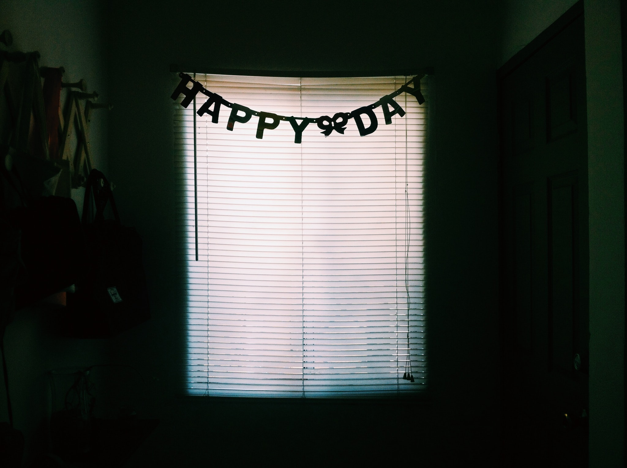 A happy birthday banner is seen hanging on the window of a darkened room.