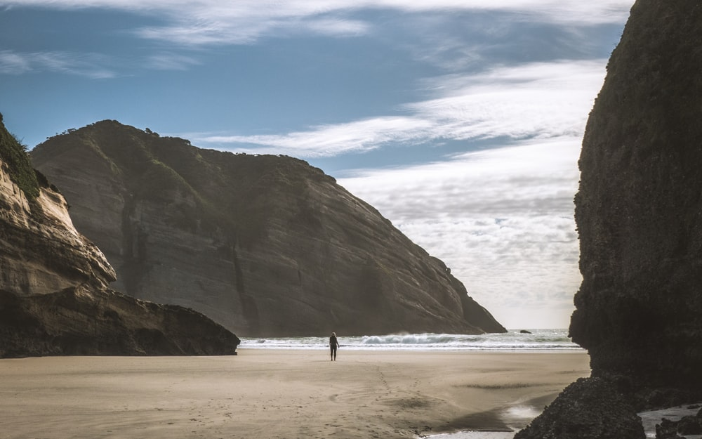 person standing on seashore between mountains