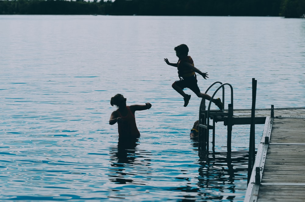 photography of boy jumping on body of water during daytime