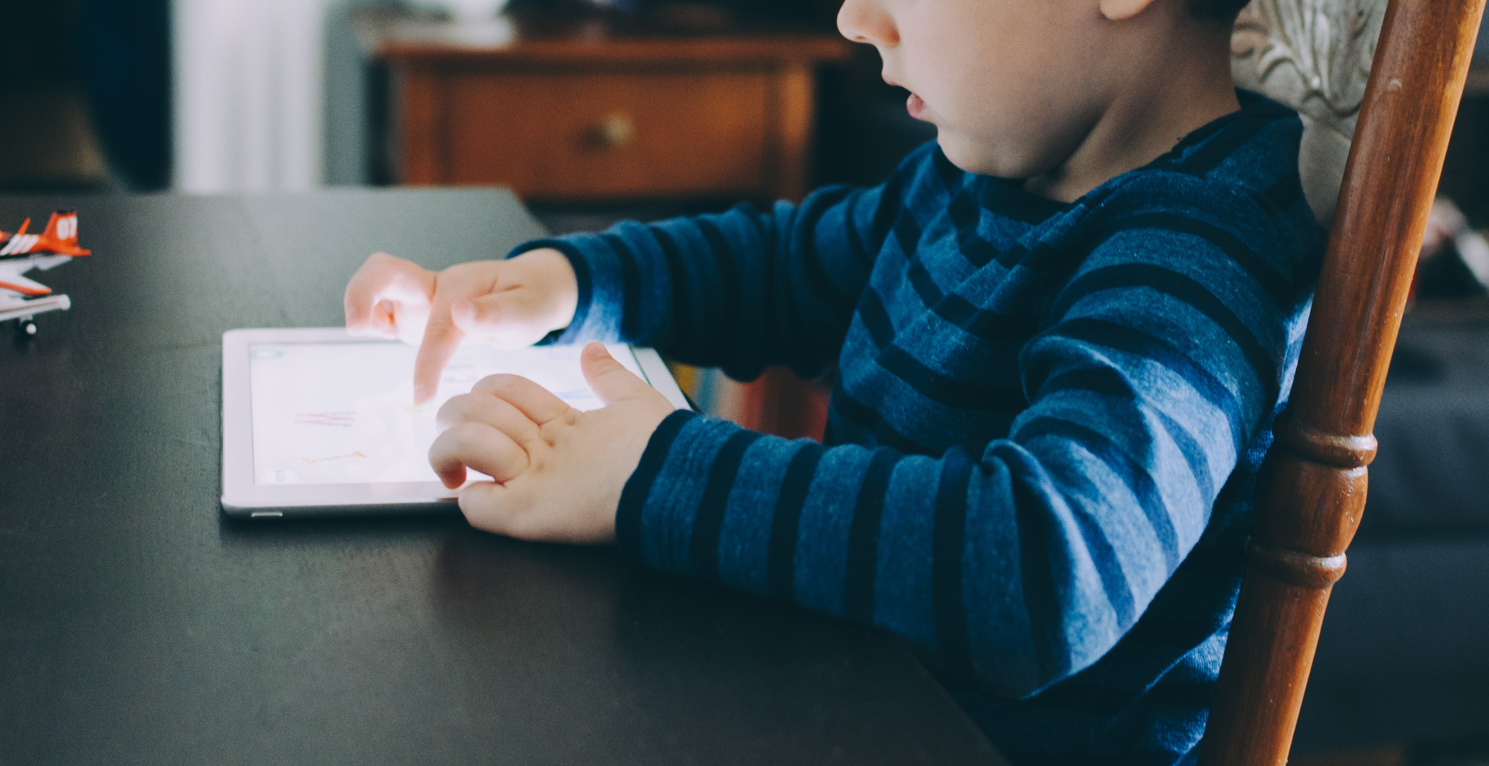 A child playing with an iPad while seated at a table