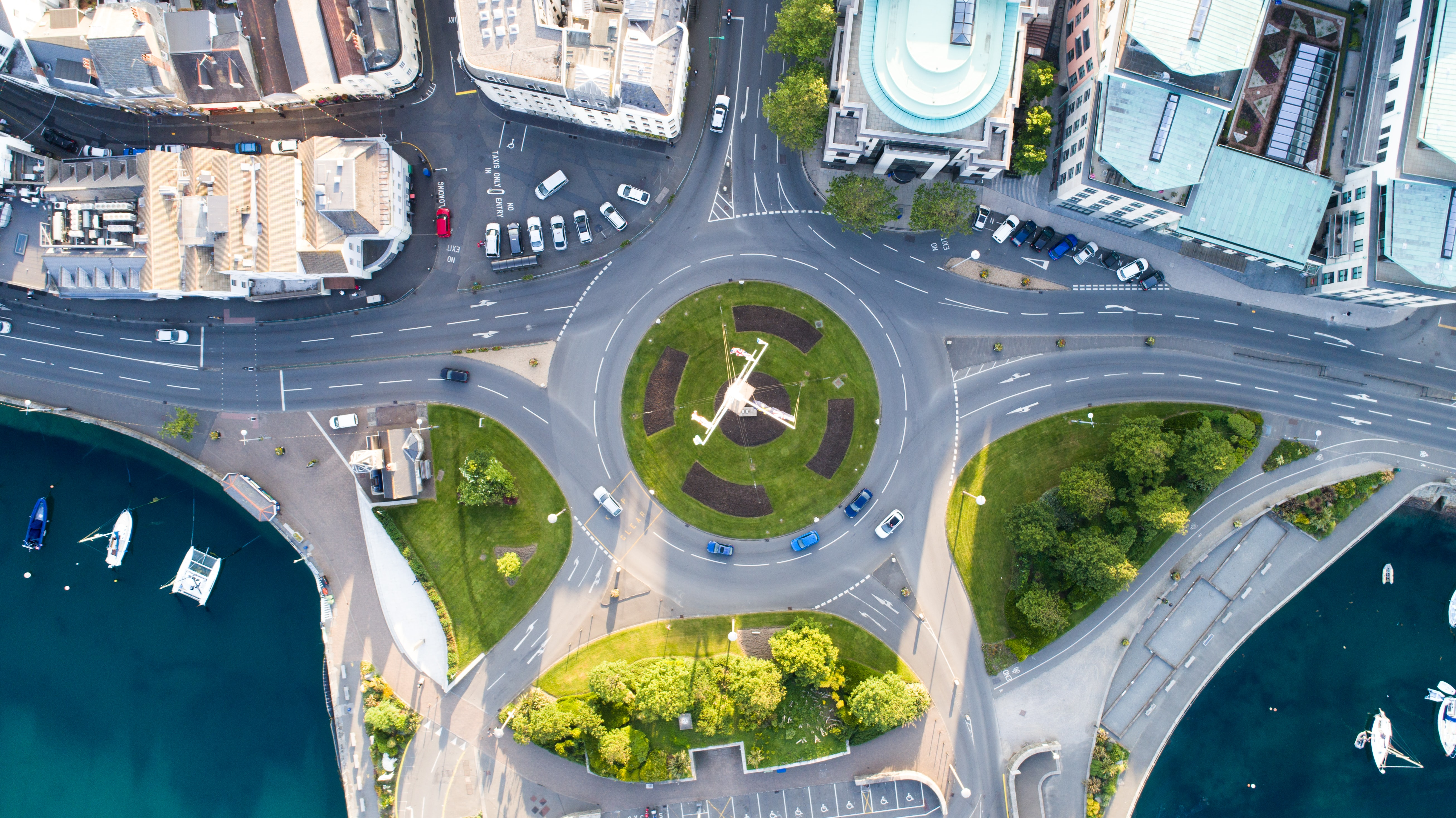 Drone view of cars going through a roundabout in the city