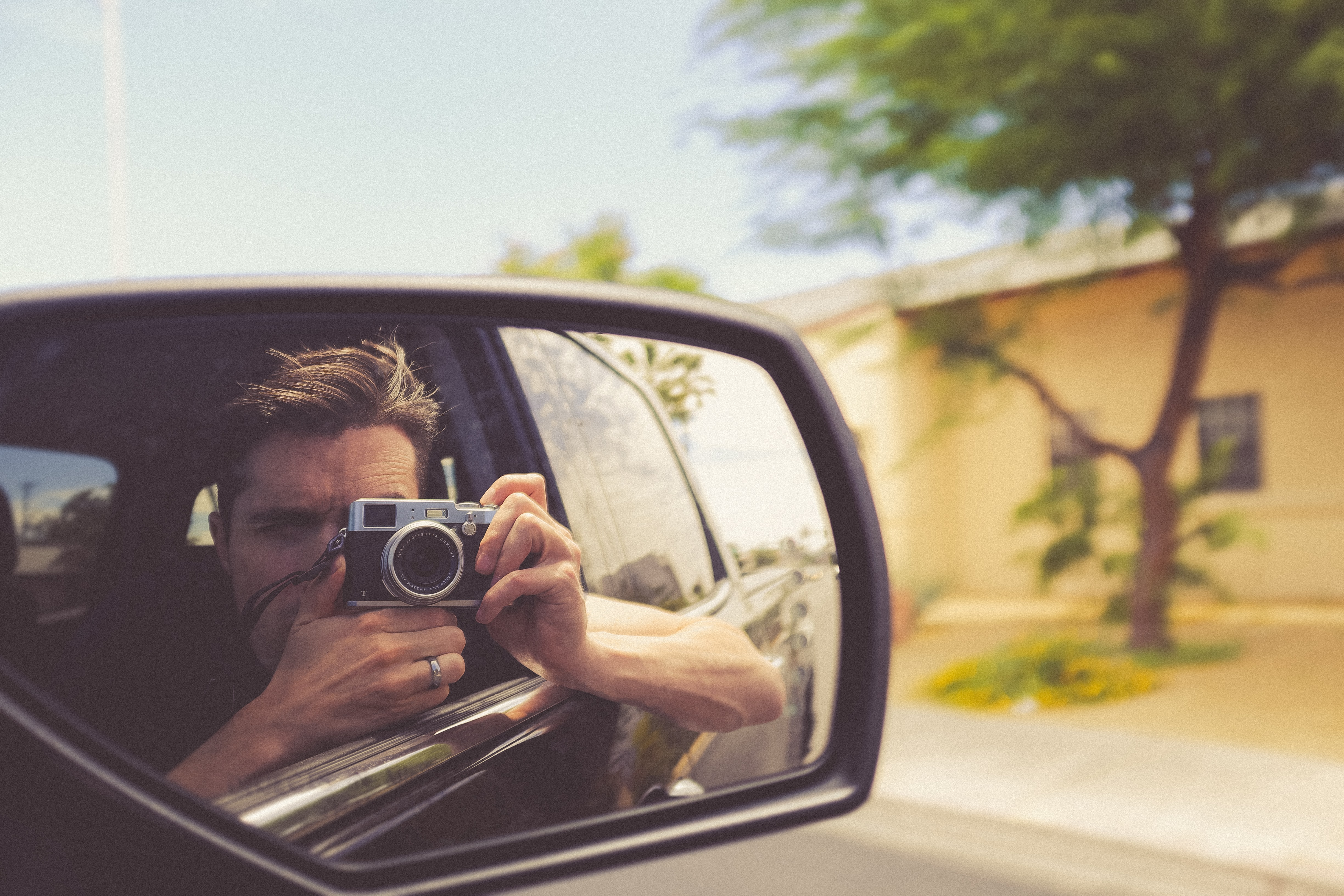 A photographer taking his self-portrait in the passenger side mirror.