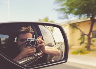 man taking car mirror shot