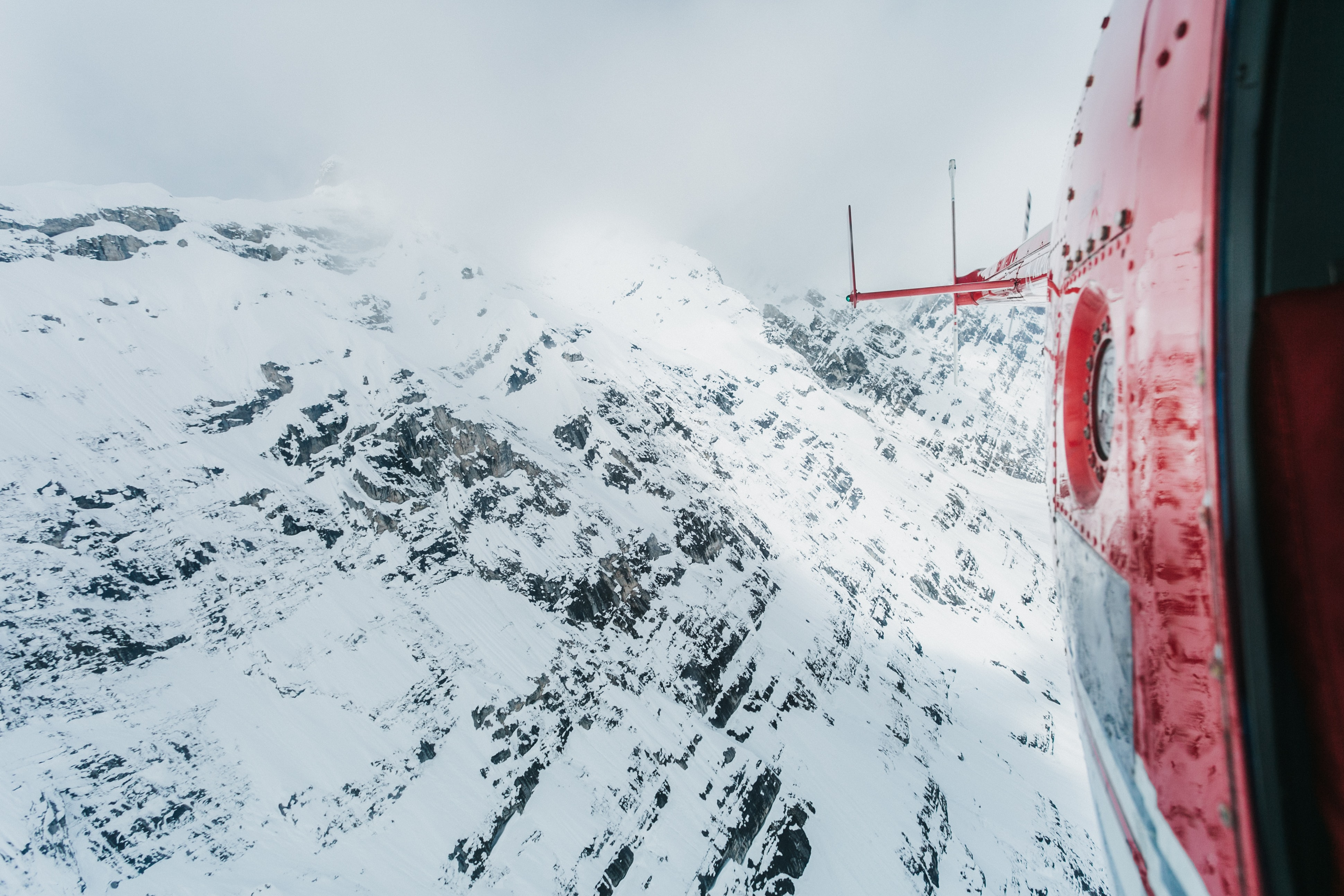 The snowy side of a mountain seen from a helicopter