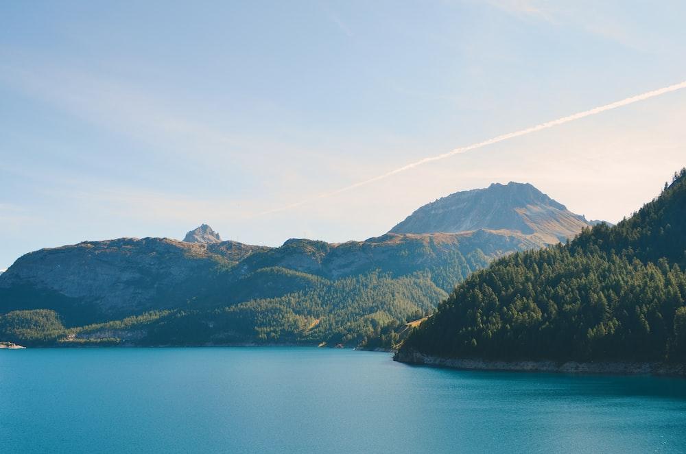 body of water near green mountain