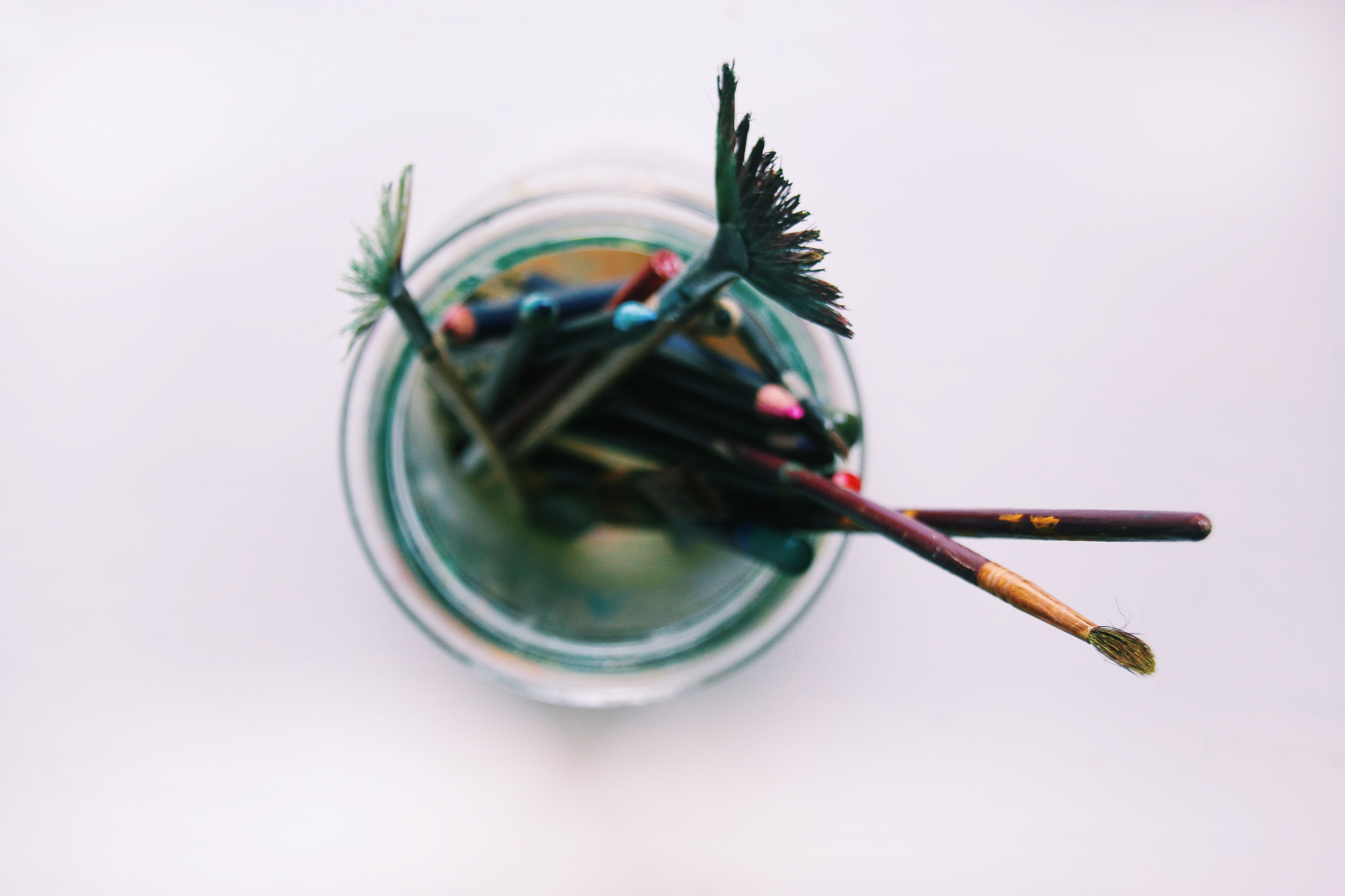 Overhead shot of dirty paint brushes in a glass on a counter