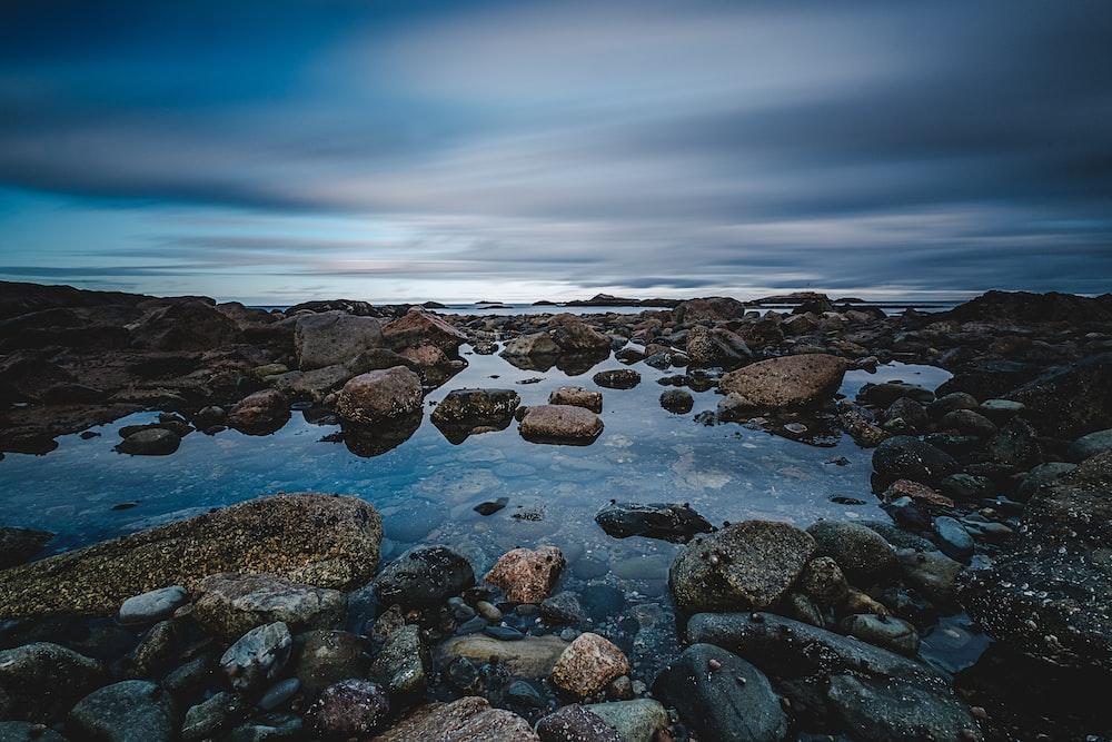 stone on coast under cumulus clouds