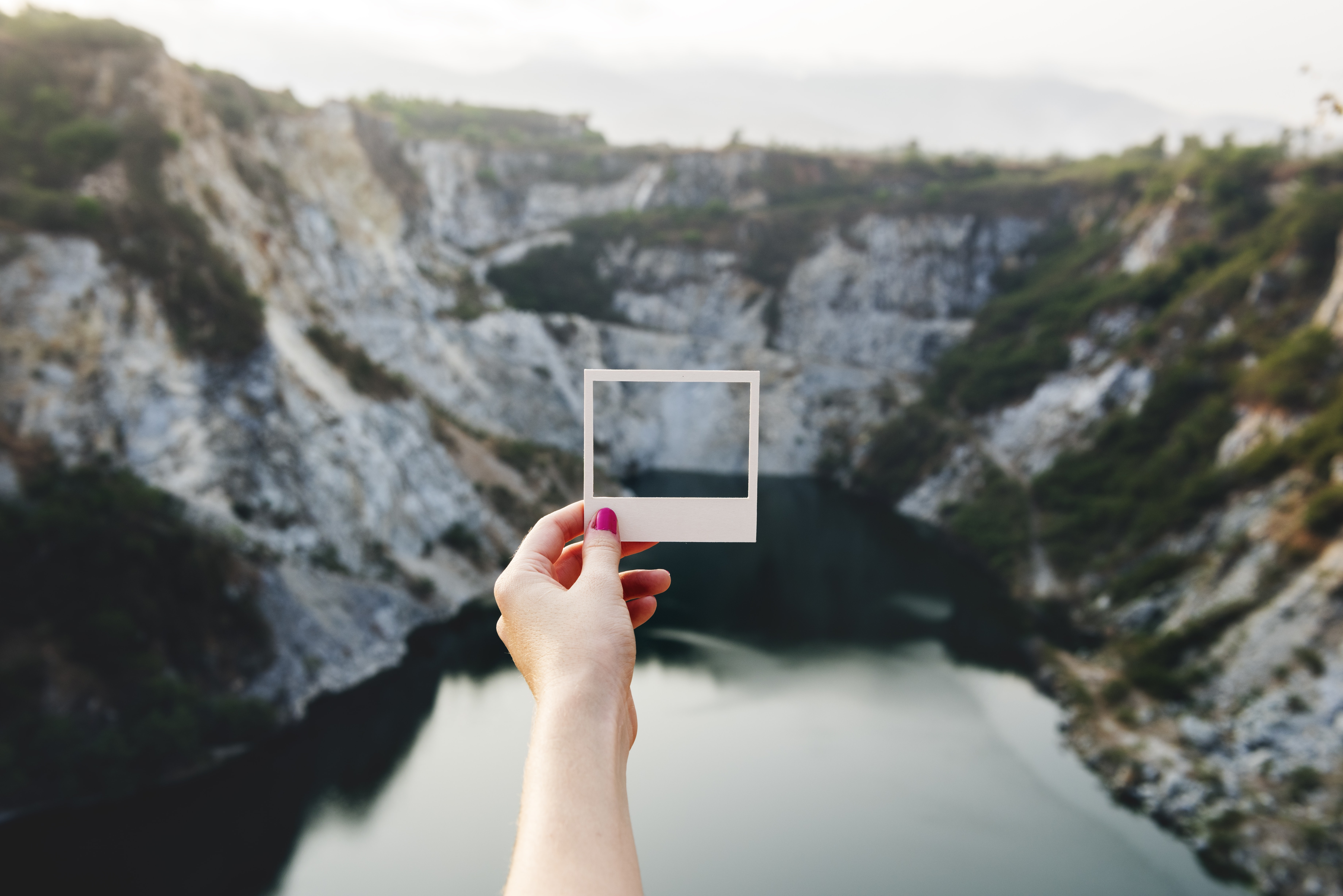 A polaroid frame is held up to a landscape