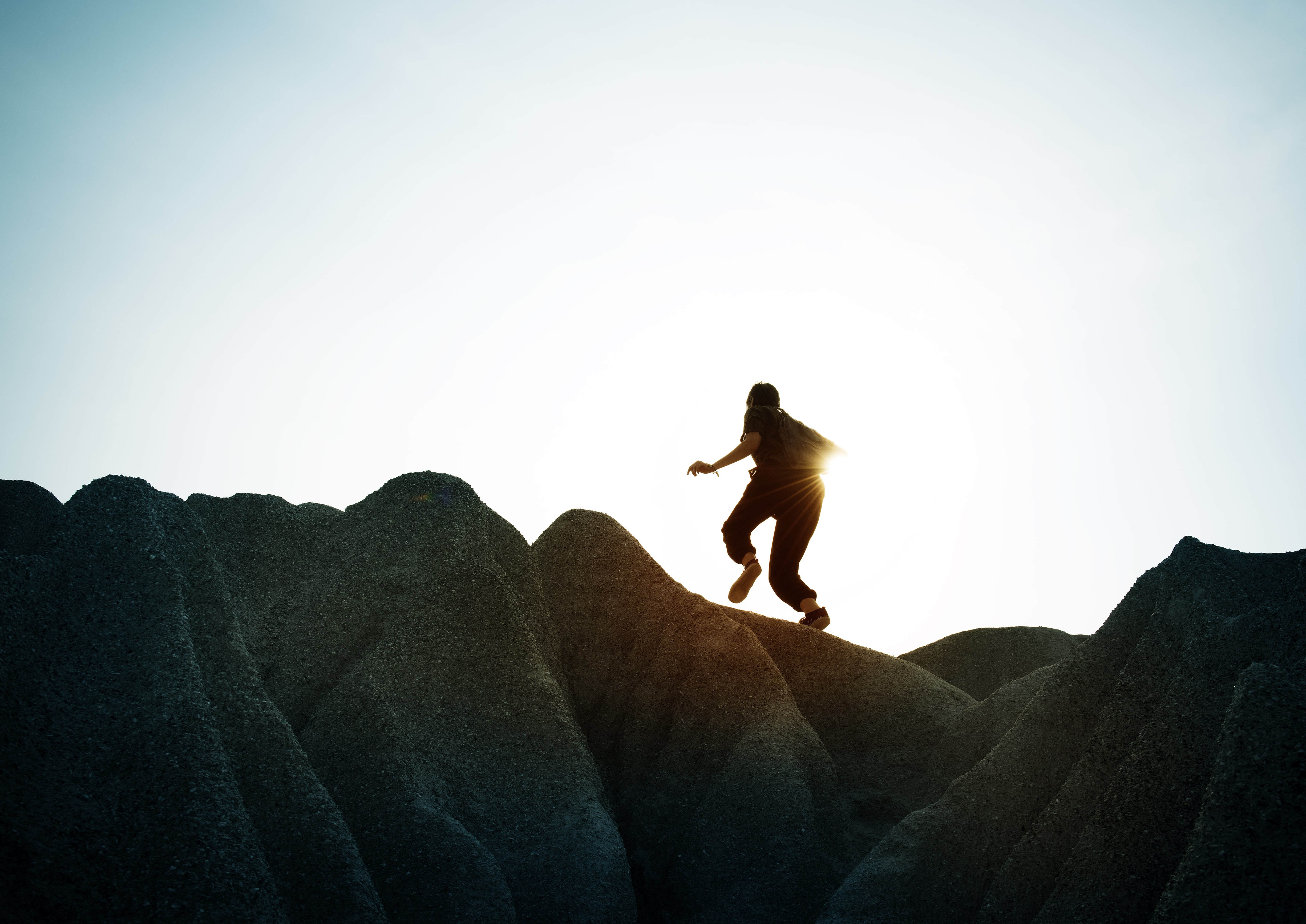 silhouette of person running on top of the mountain
