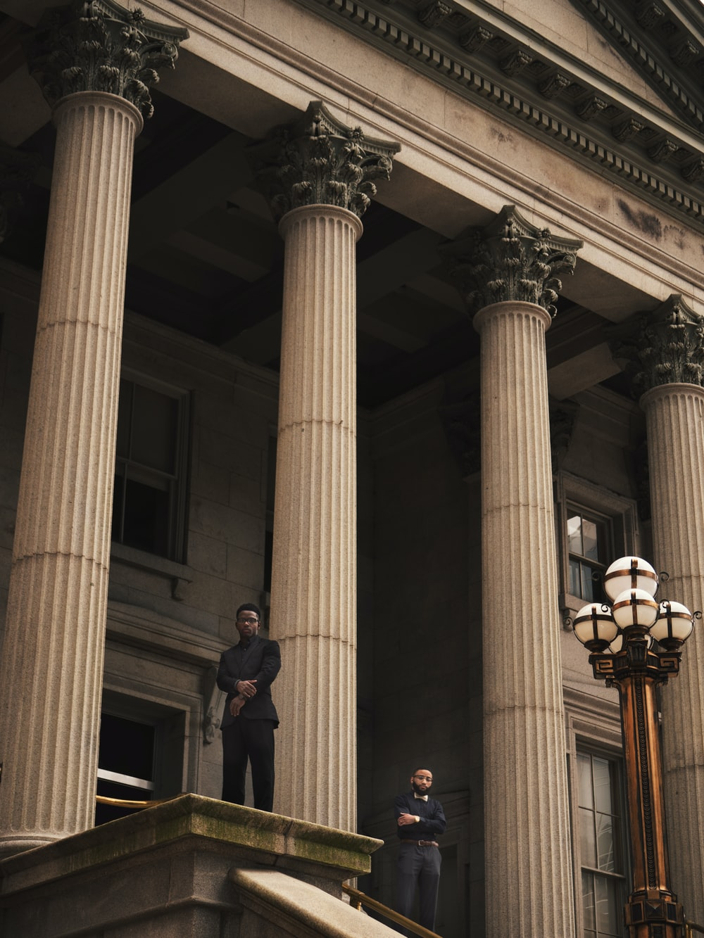 two men standing on Corinthian column building